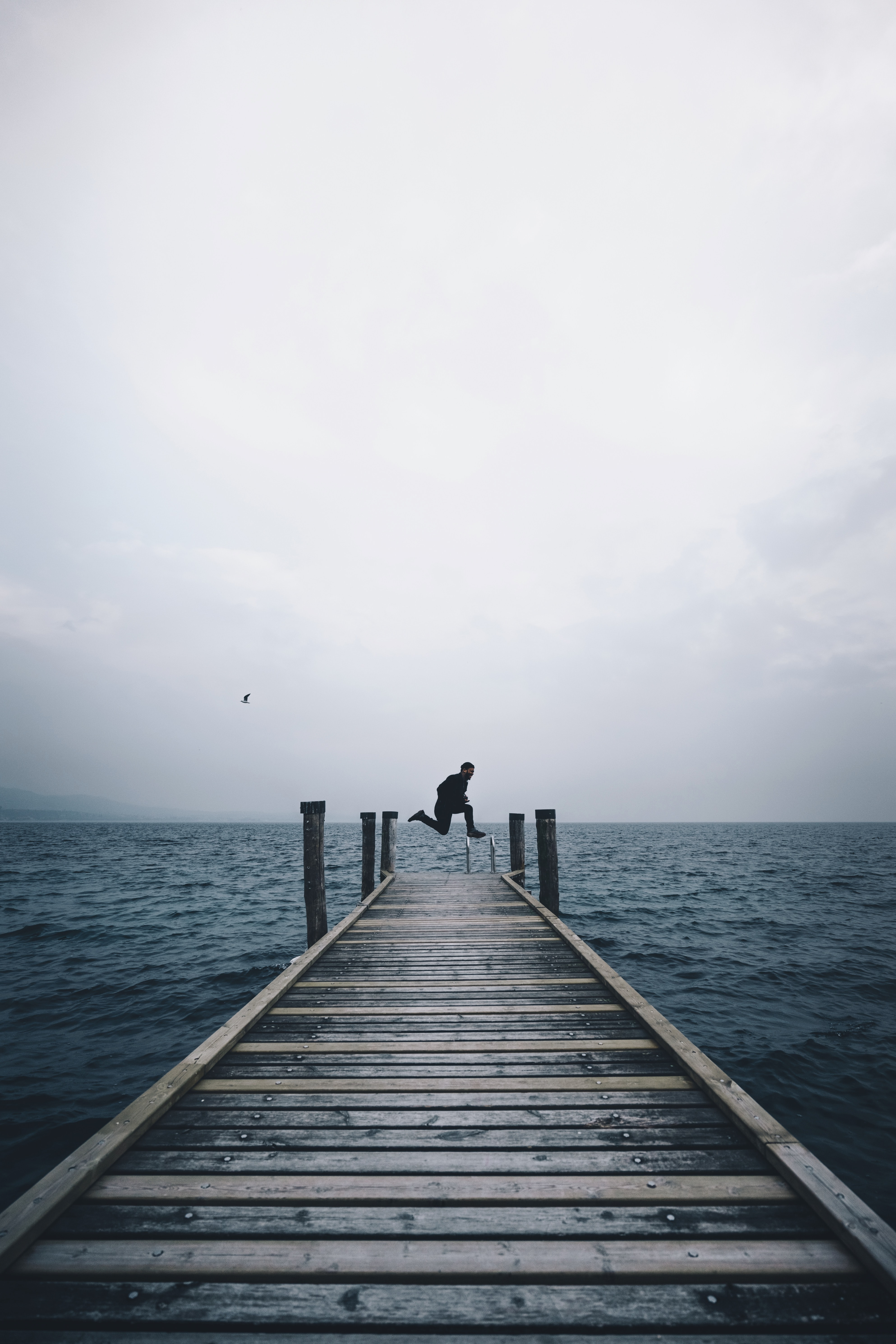 A person jumping in the air on the edge of a dock by a lake in Punta Saint Vigilio on a cloudy day