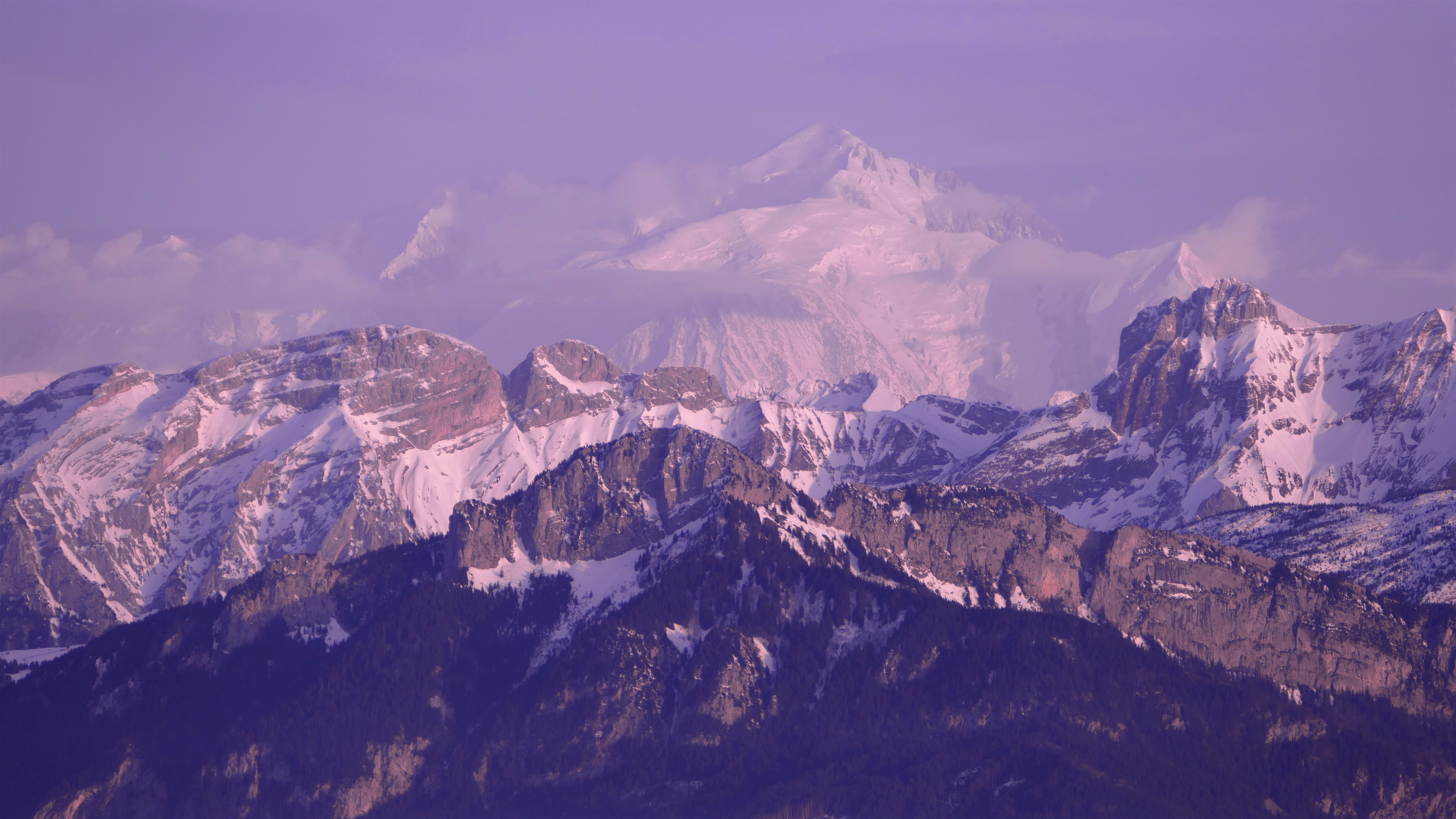 A purple-hued shot of the mighty Mont Blanc towering over granite ridges