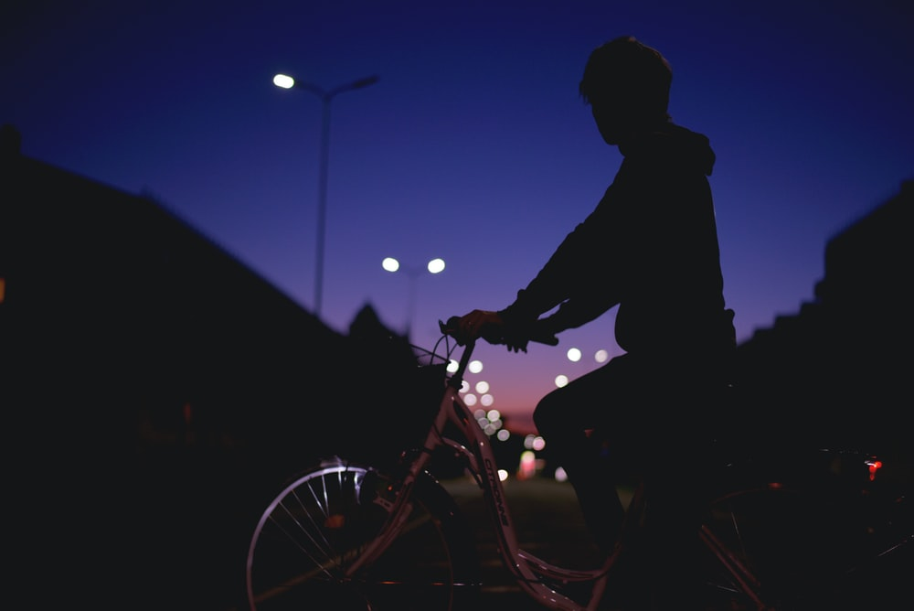 silhouette person riding on bike at night