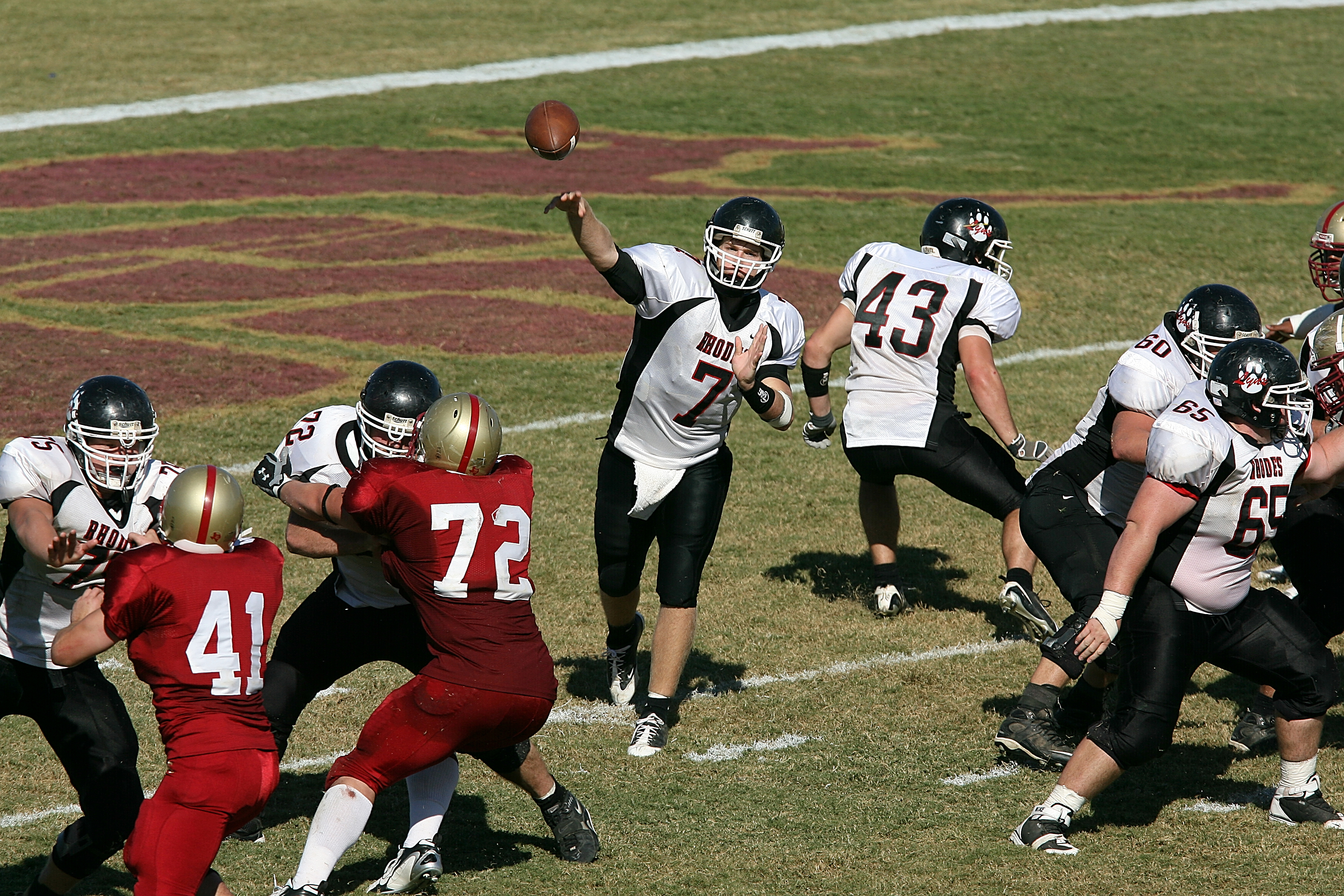 College quarterback passes the football while his teammates protect him from onrushing opponents.