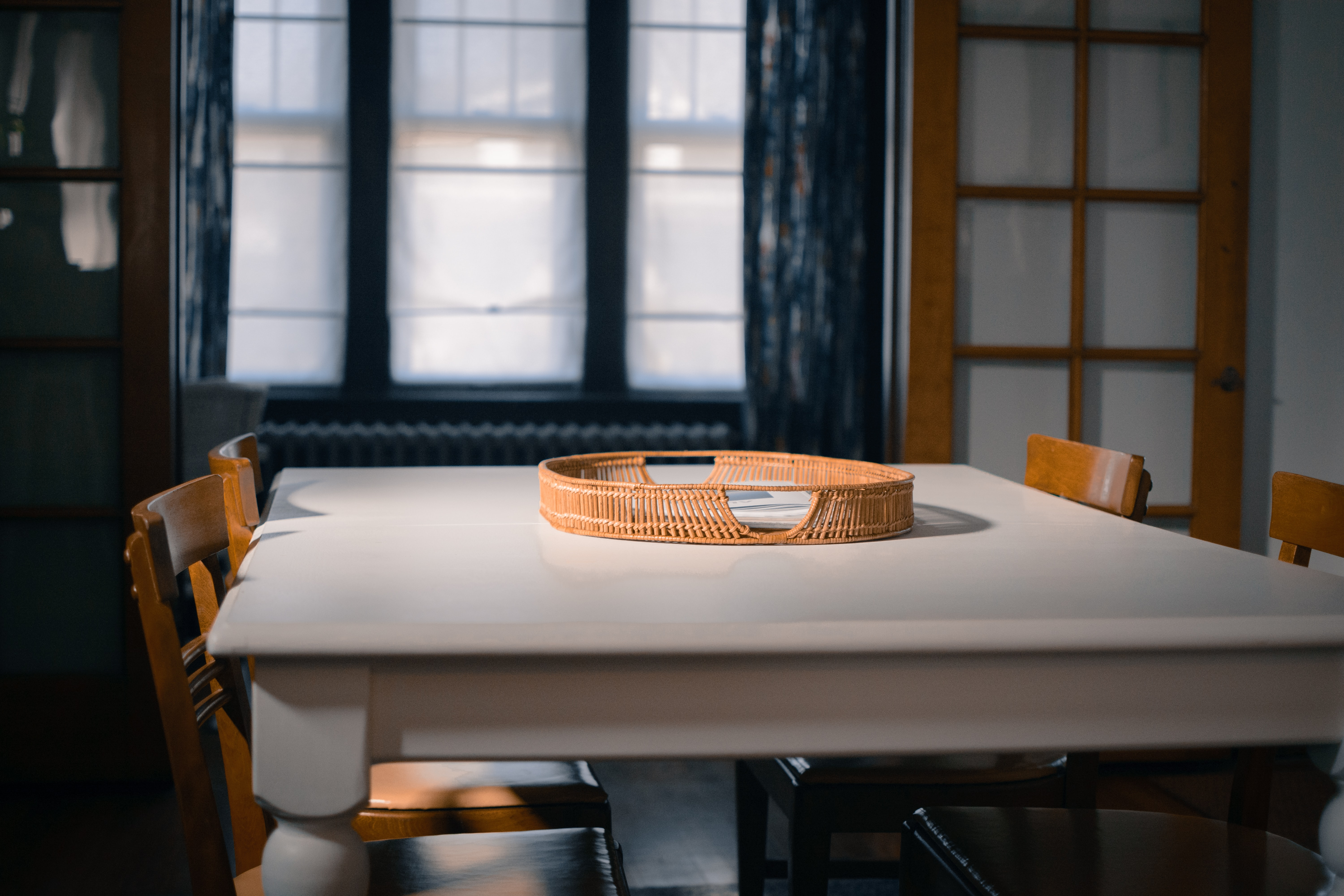 An empty rattan tray sits in the middle of a wooden dinning table set in St. Louis