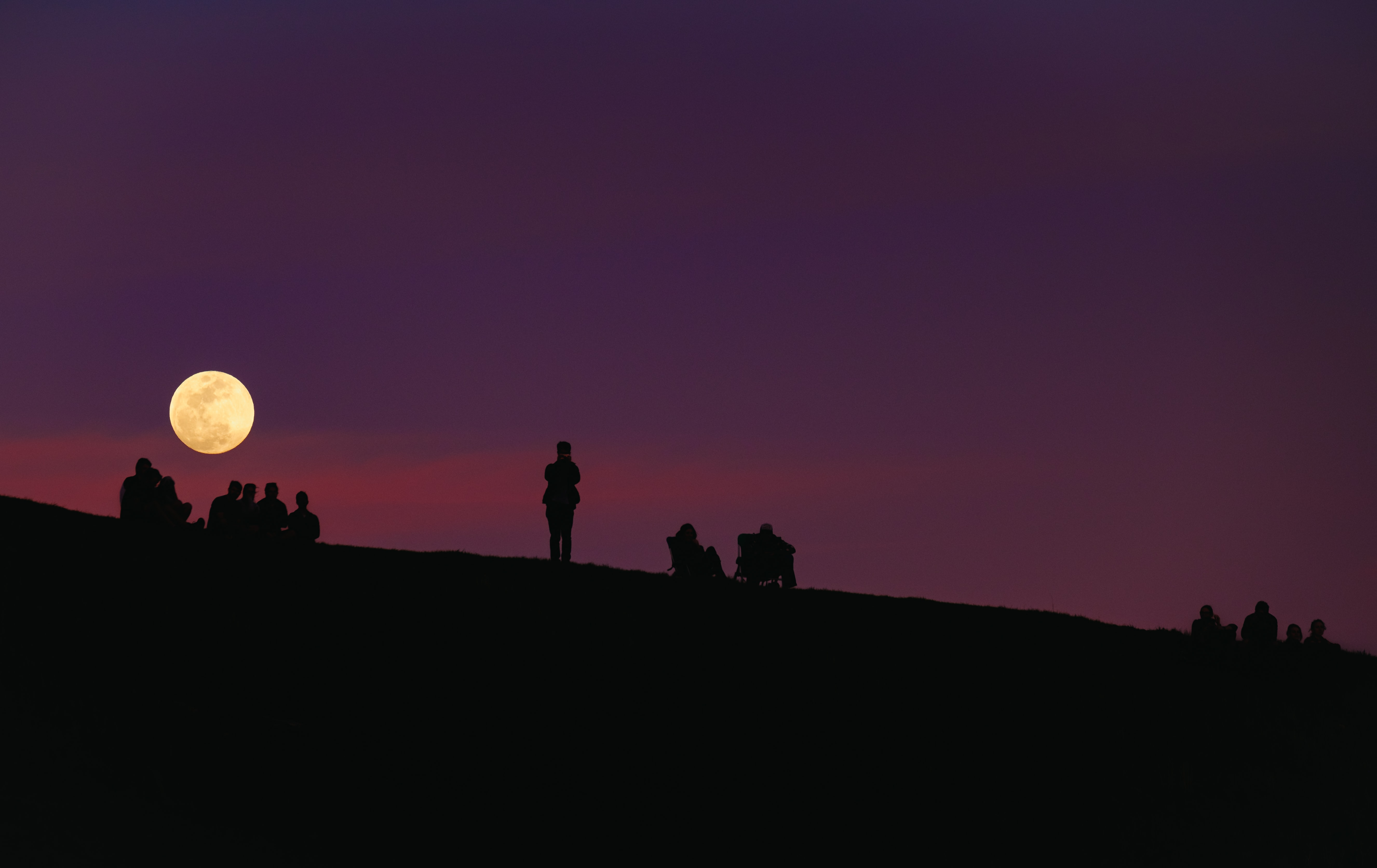 Moon rises on a purple sky over silhouettes of people on the slope of Mount Tamalpais