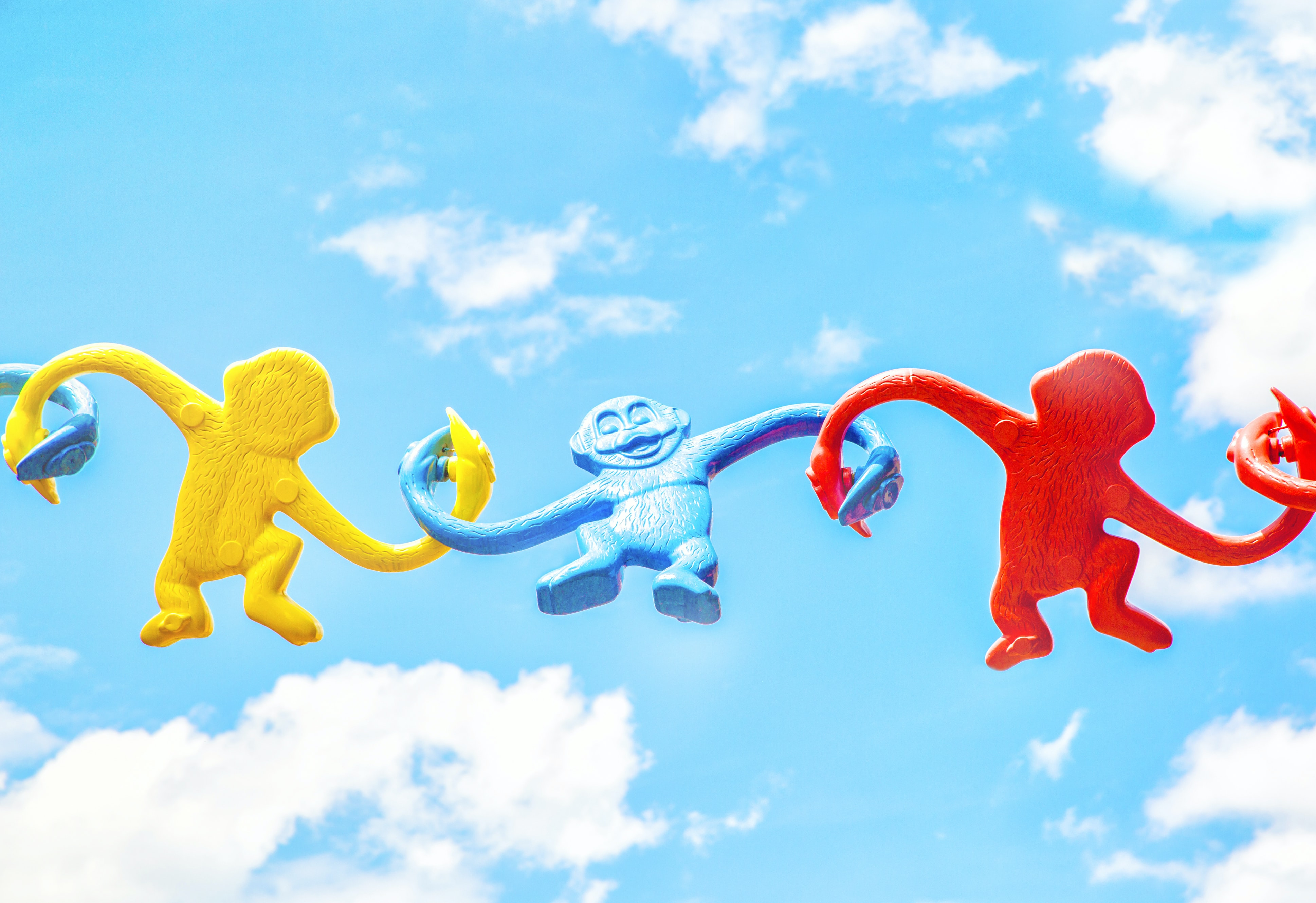 Yellow, blue and red plastic monkeys holding their hands against a blue sky