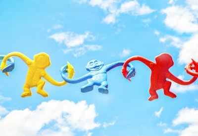 three assorted-color monkey plastic toys holding each other during daytime fun zoom background