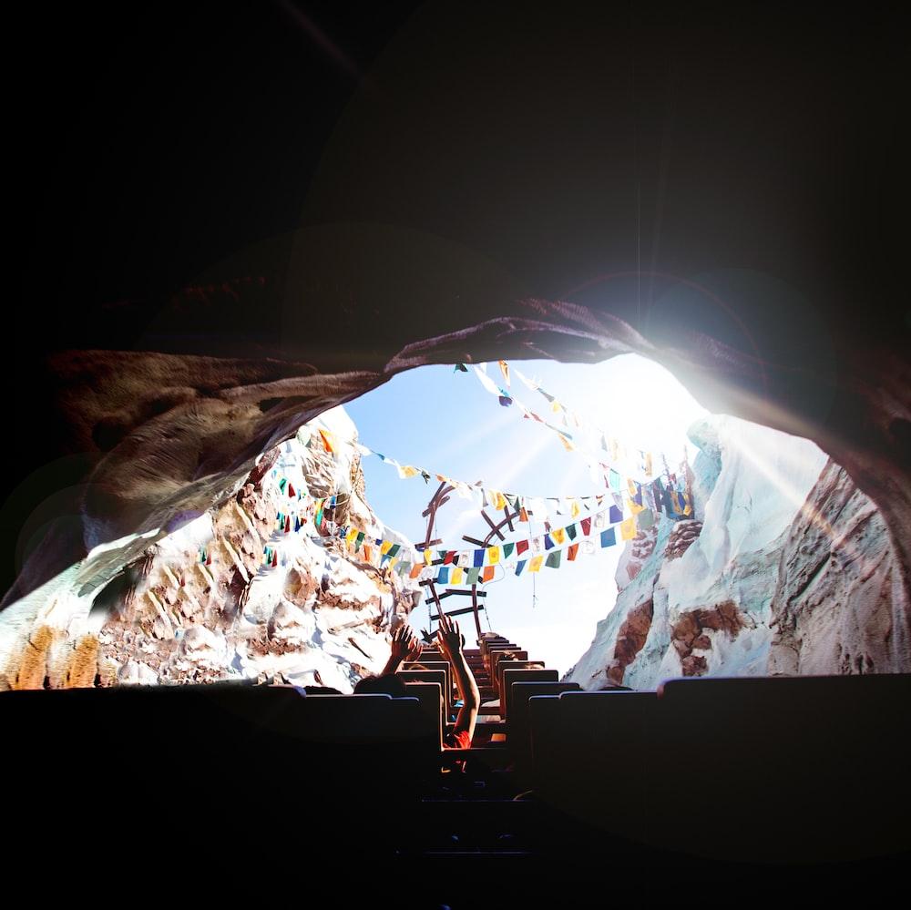 person riding roller coaster entering a hole