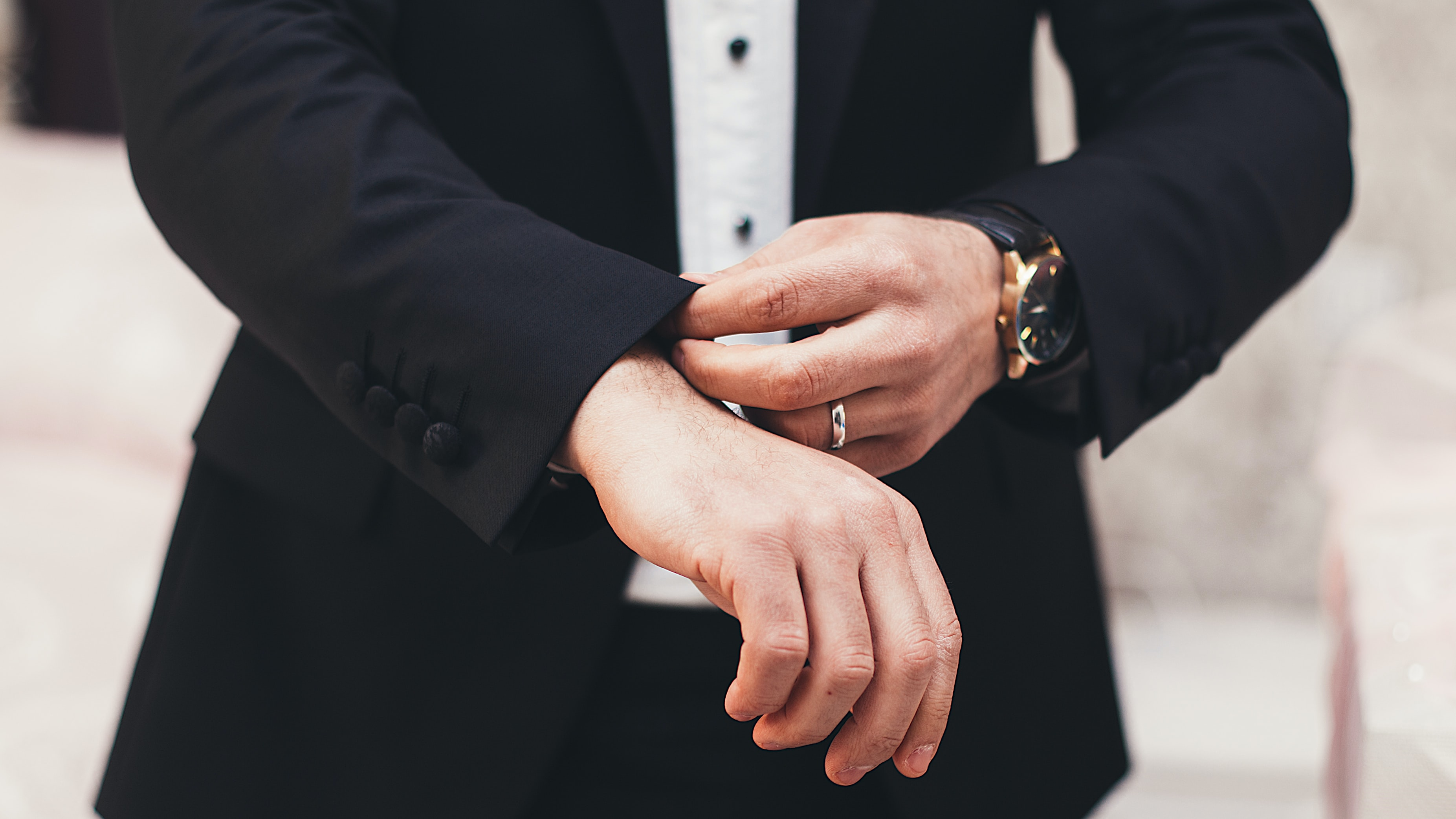 A man's hands adjusting the cuffs of his black suit