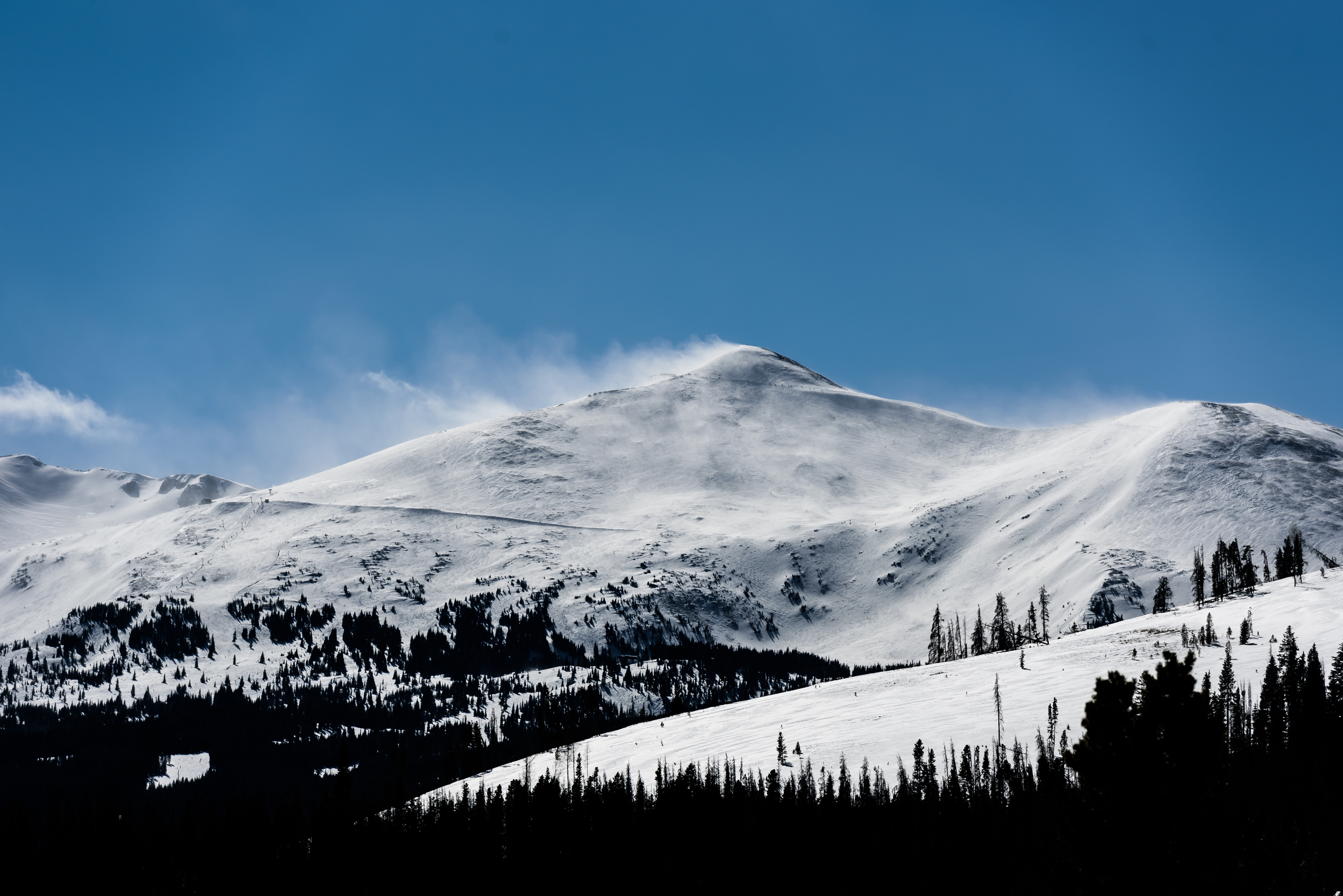 snow capped mountain under blue skies