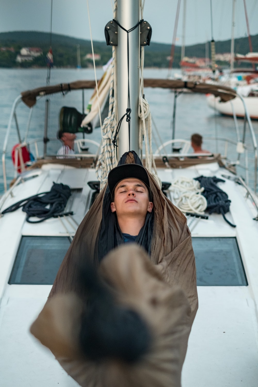 man sleeping on boat hammock