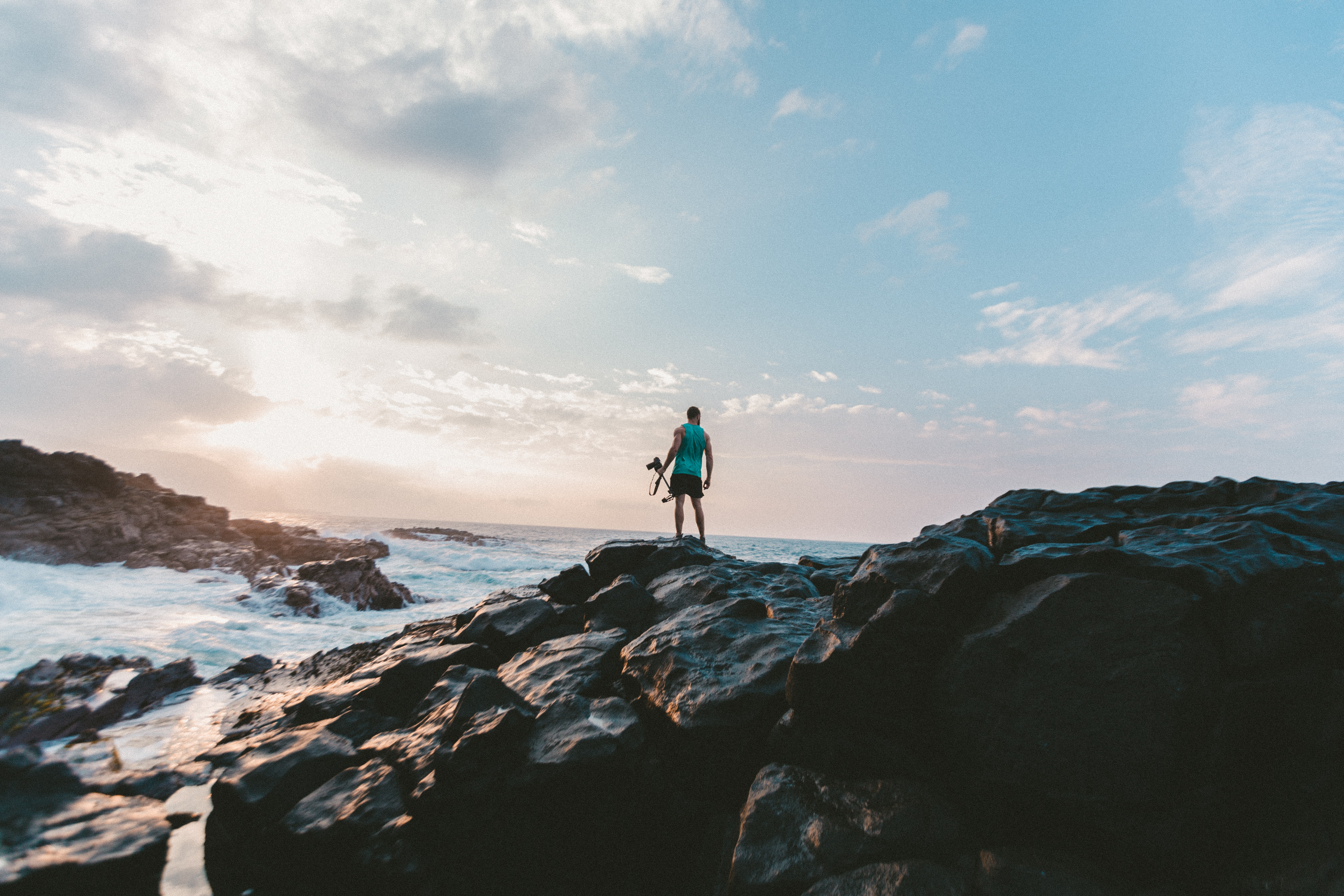man standing on rocky shore under cloudy sky