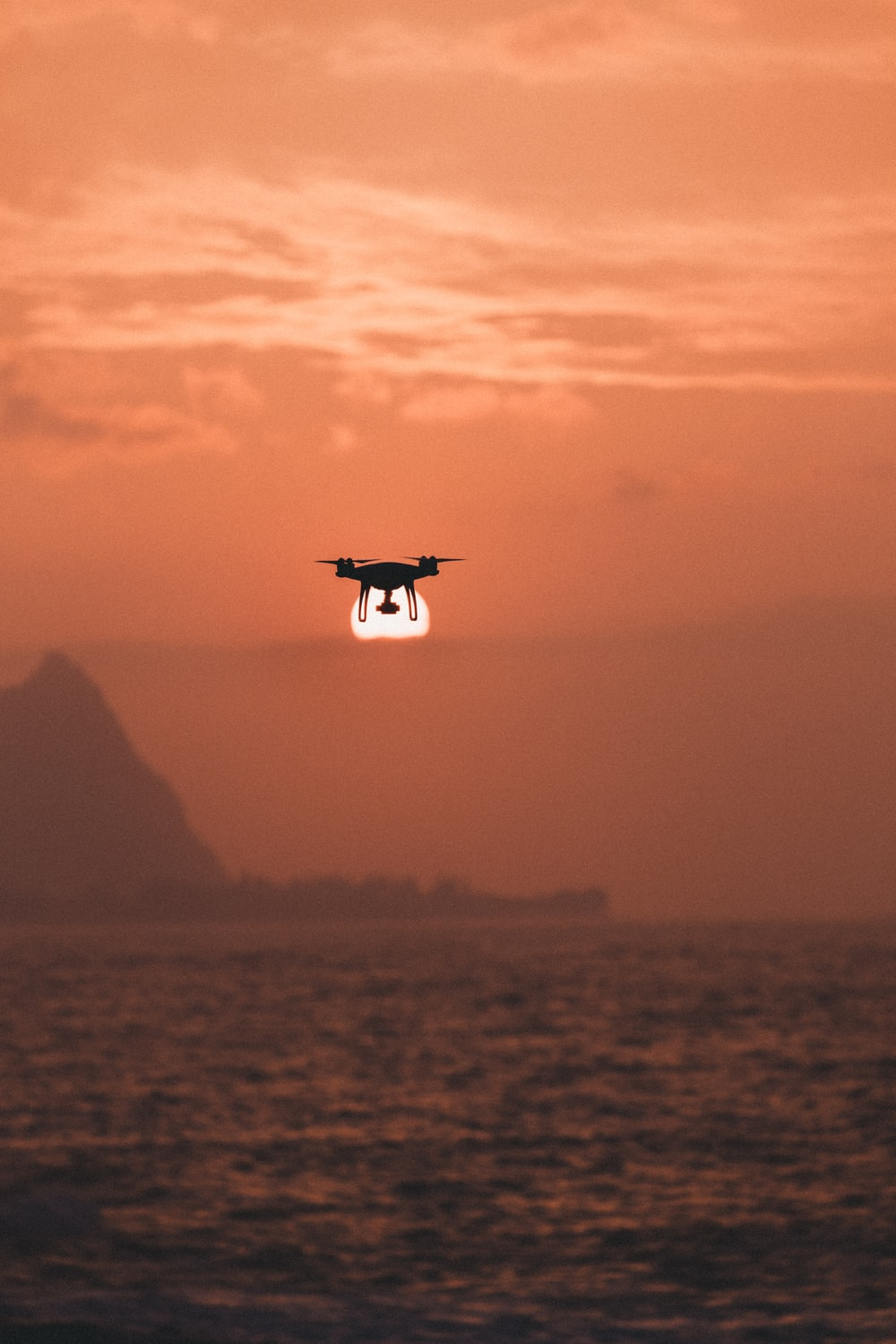 silhouette of drone hovering above body of water