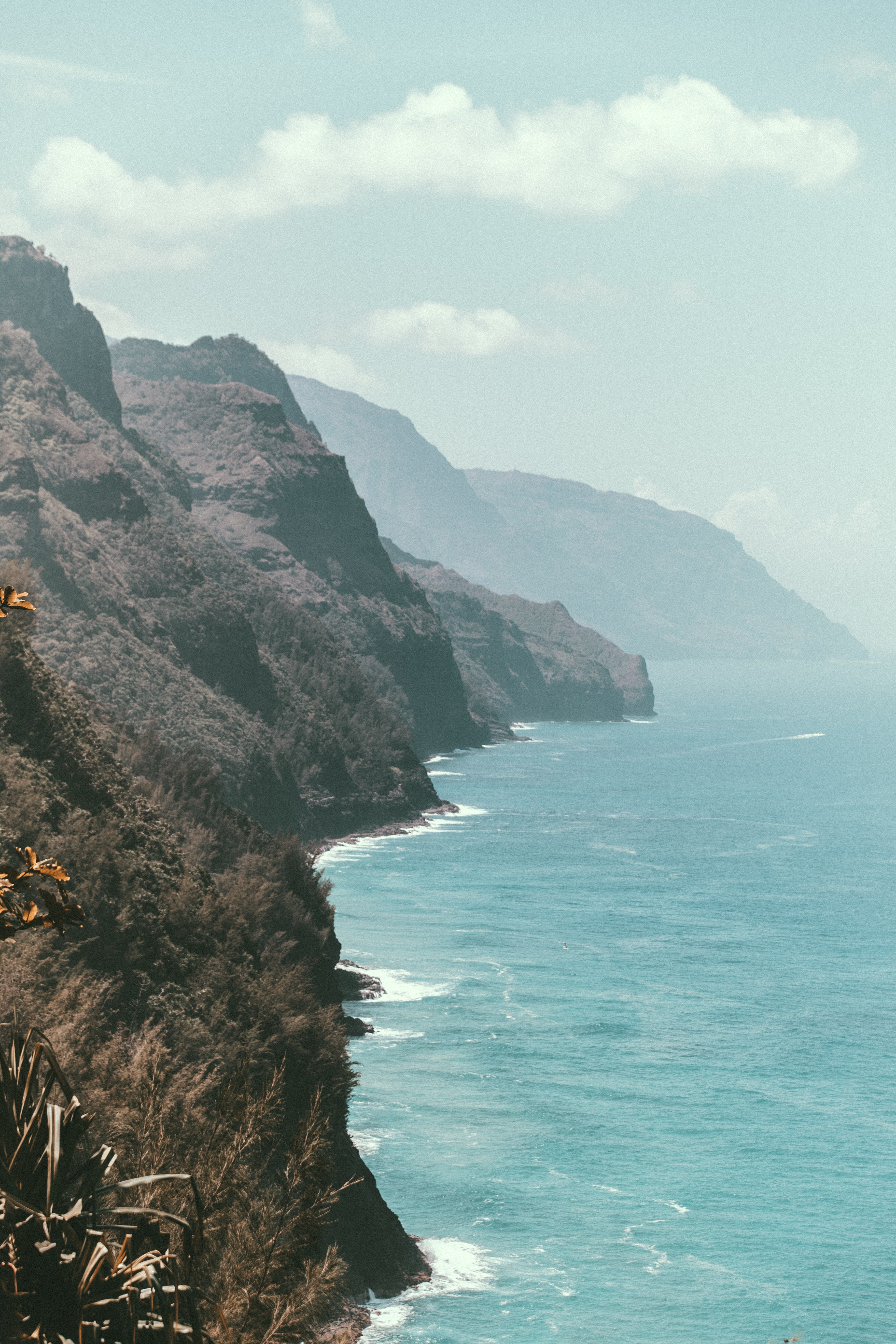 The side of a rocky cliff along a bright blue ocean in Kauai