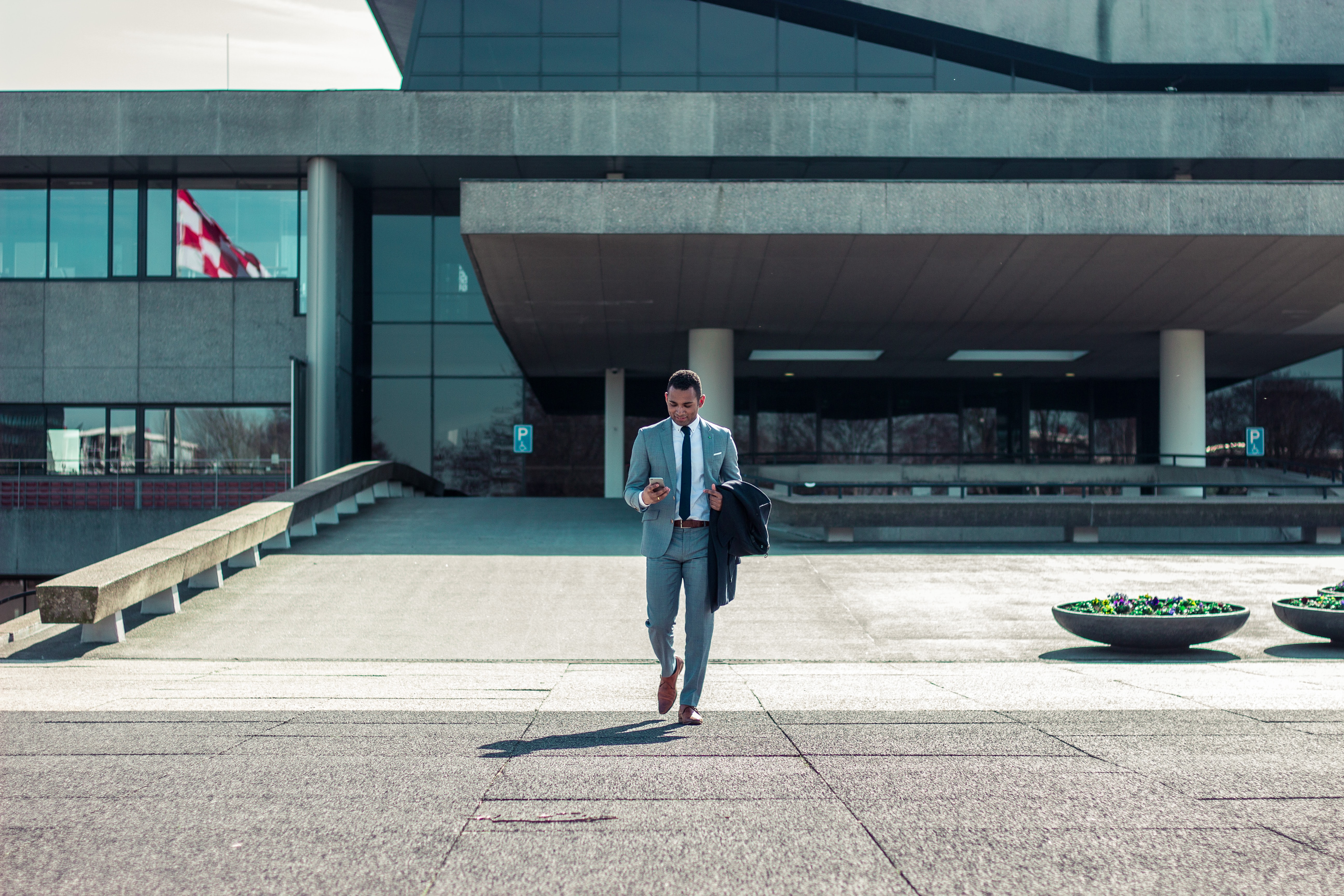 A man in a formal suit checking his smartphone while walking out of an office building