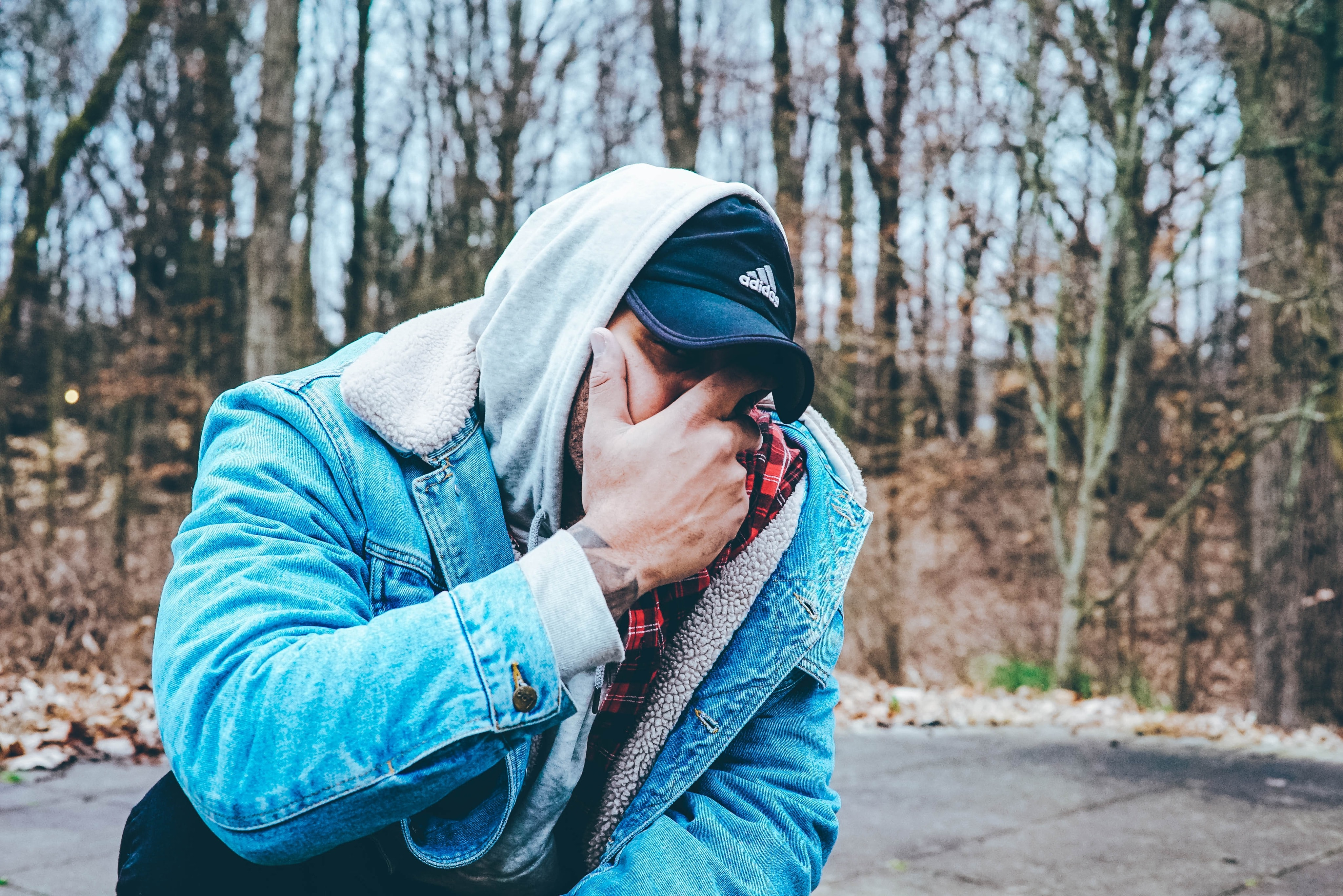 man in blue denim jacket covering his mouth with hand