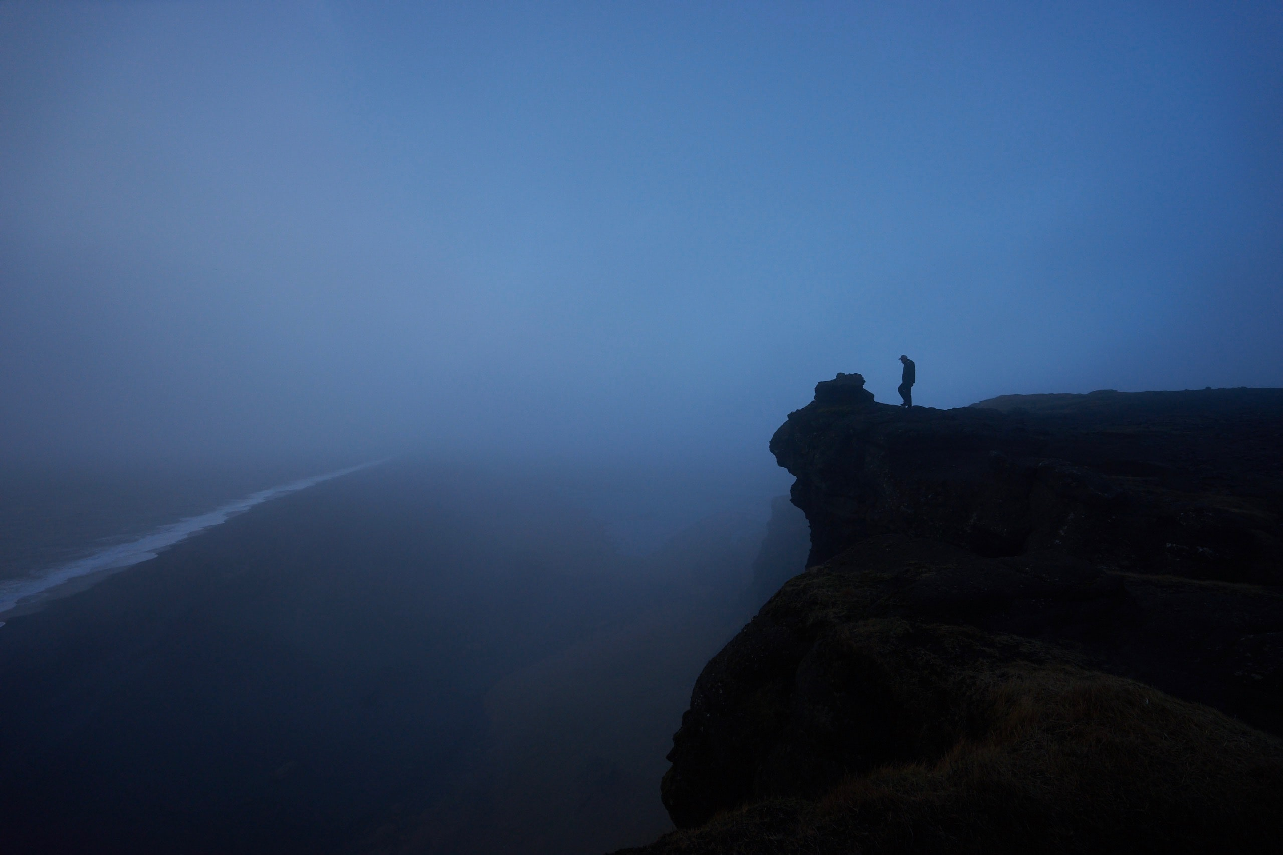 Silhouette of person on a mountain ledge near a misty shore
