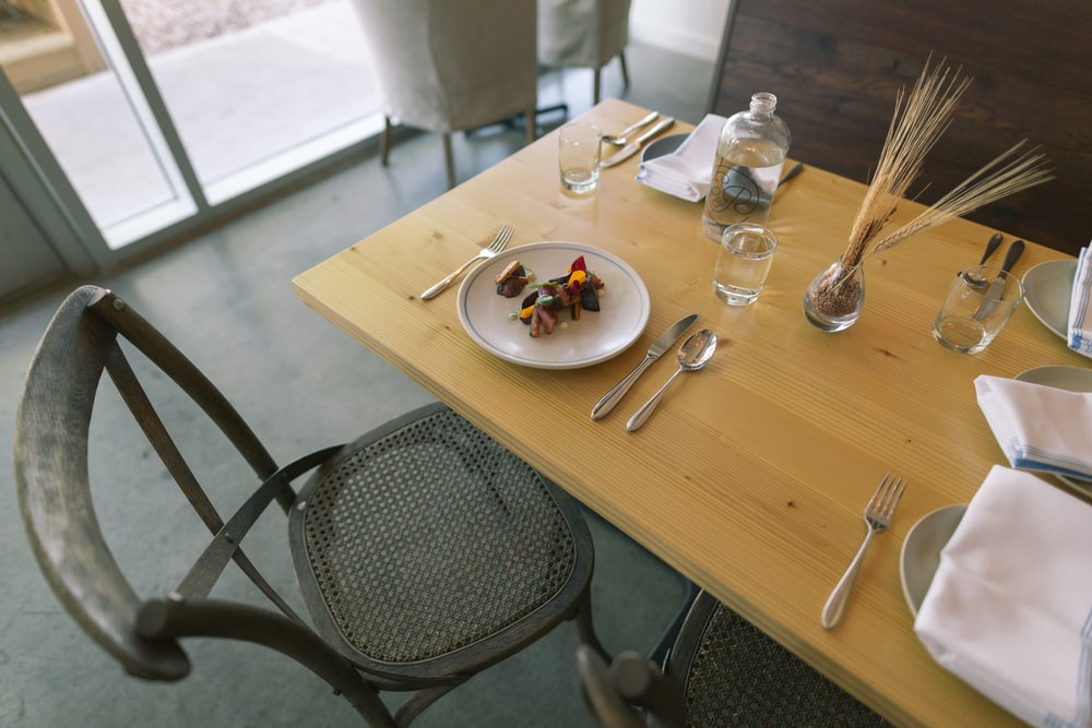 white ceramic plate and silver flatware on table