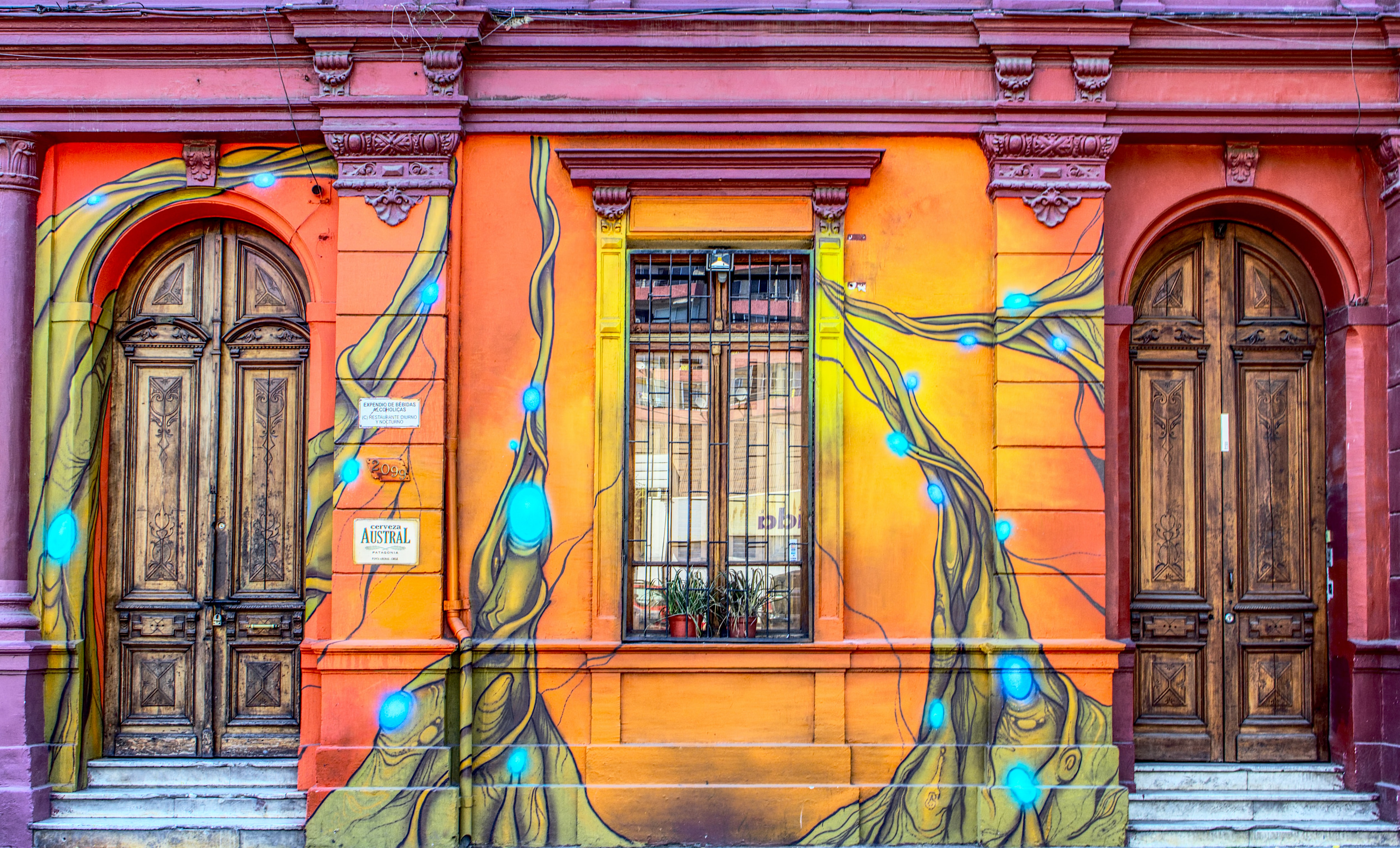 Colorful sunburst wall art on building wall with windows and wooden doors, Santiago