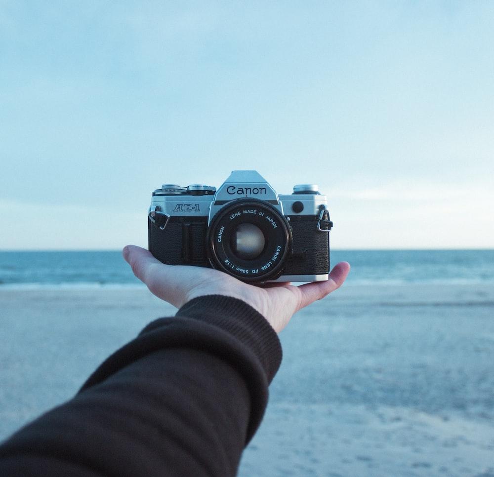 person holding black and gray Canon AE-1 bridge camera