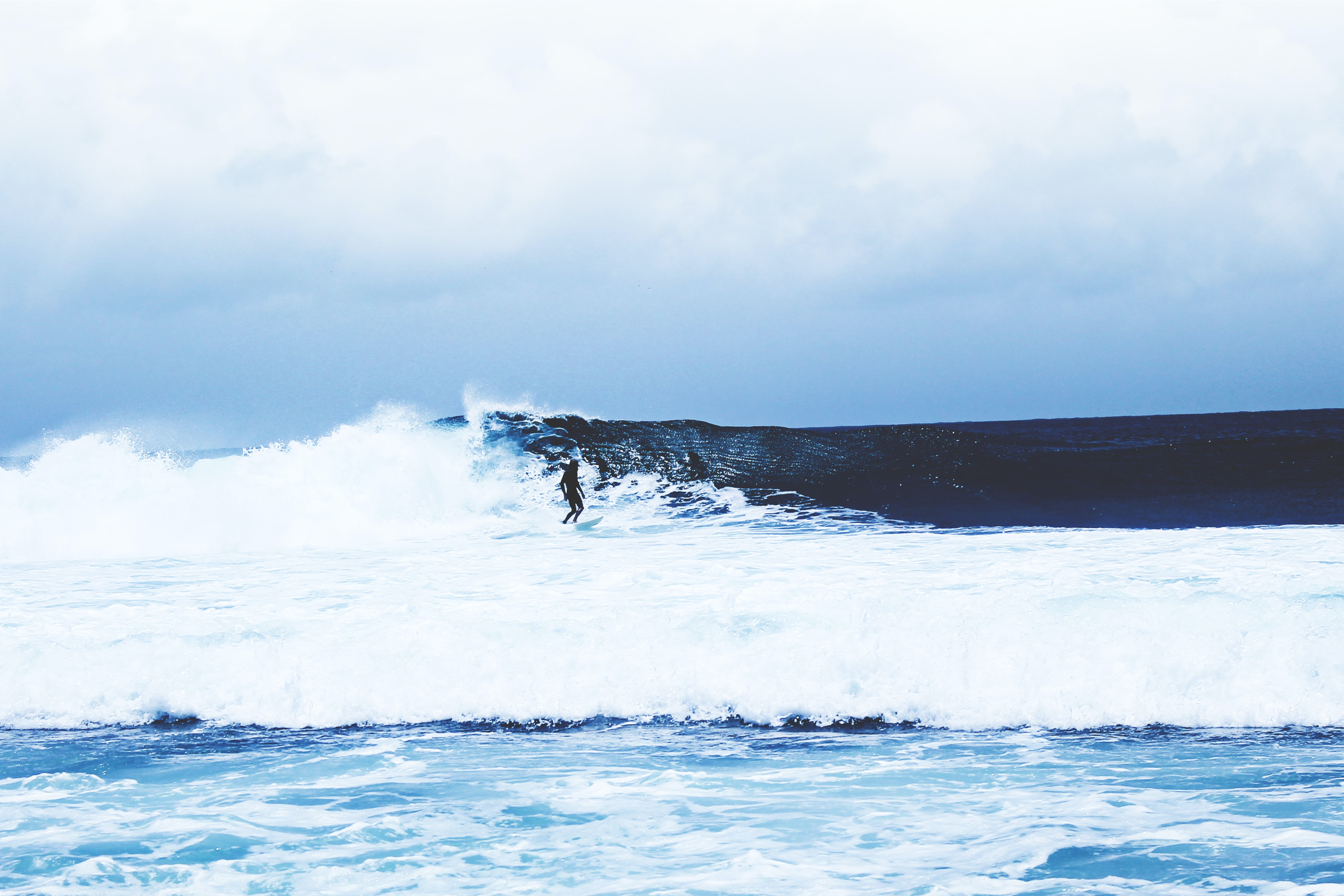 A distant surfer riding a rough ocean wave in West Java