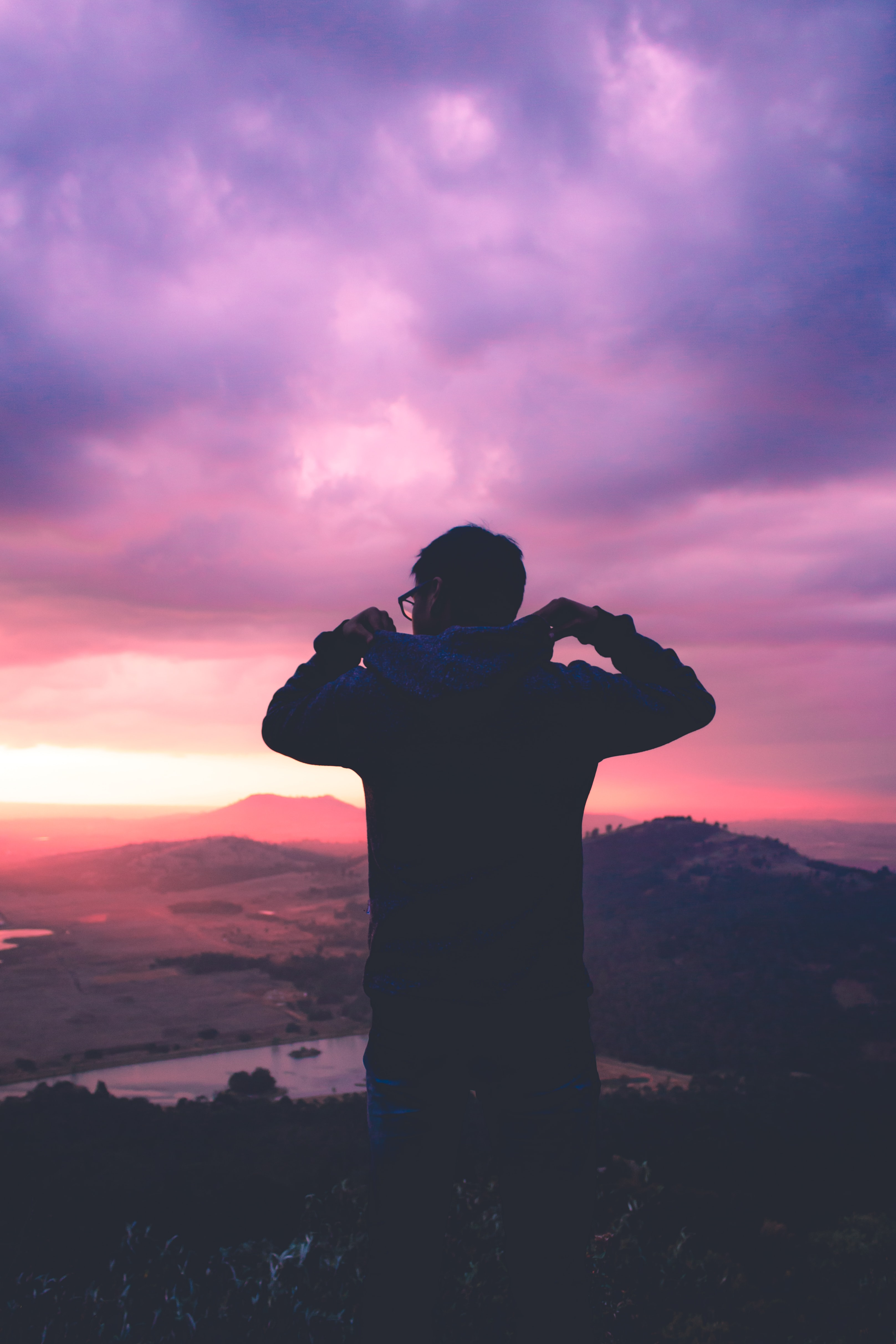 A silhouette of a man looking out at a pink sunset and purple cloudy sky in Toluca, Mexico