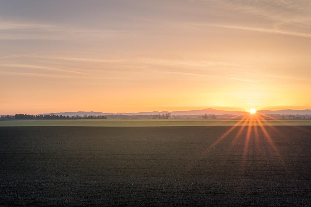 brown soil field across mountain under orange sunset sky
