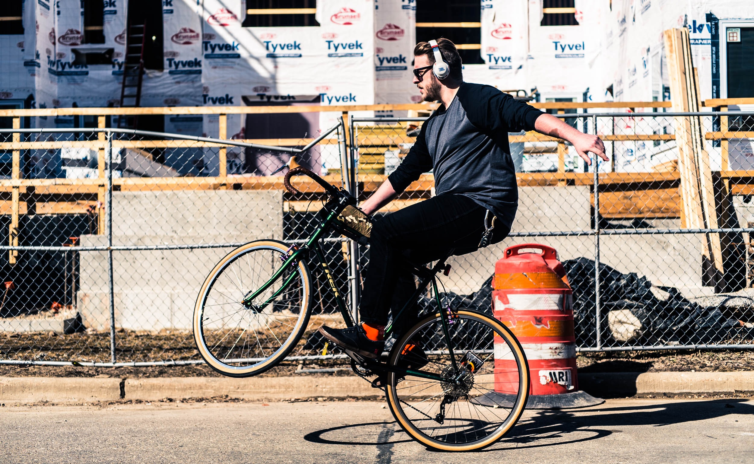 A bearded man wearing headphones does a wheelie on a bicycle by a construction site