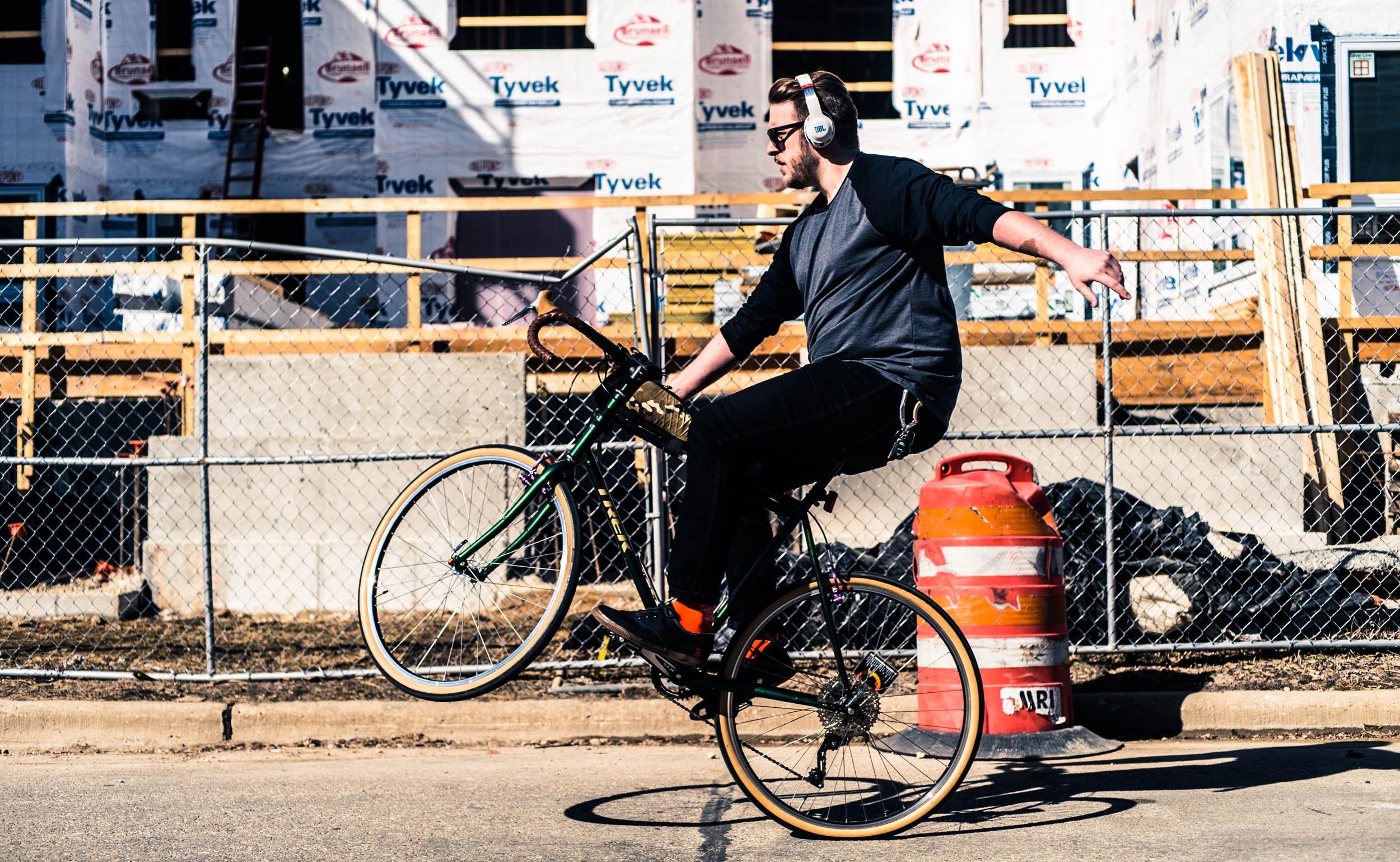 man riding on bicycle using headphones