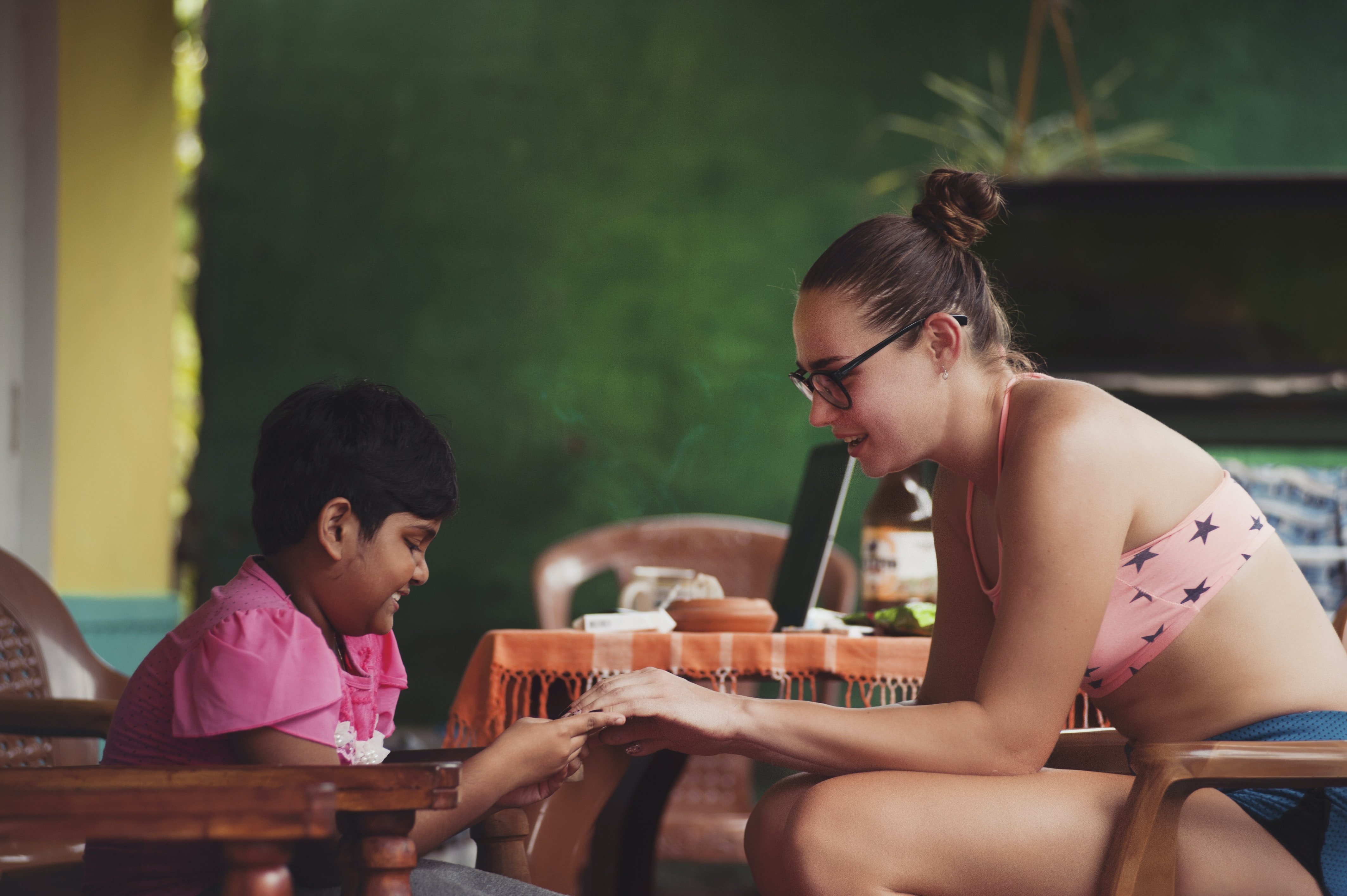 A woman and a child sitting in chairs opposite to each other and playing