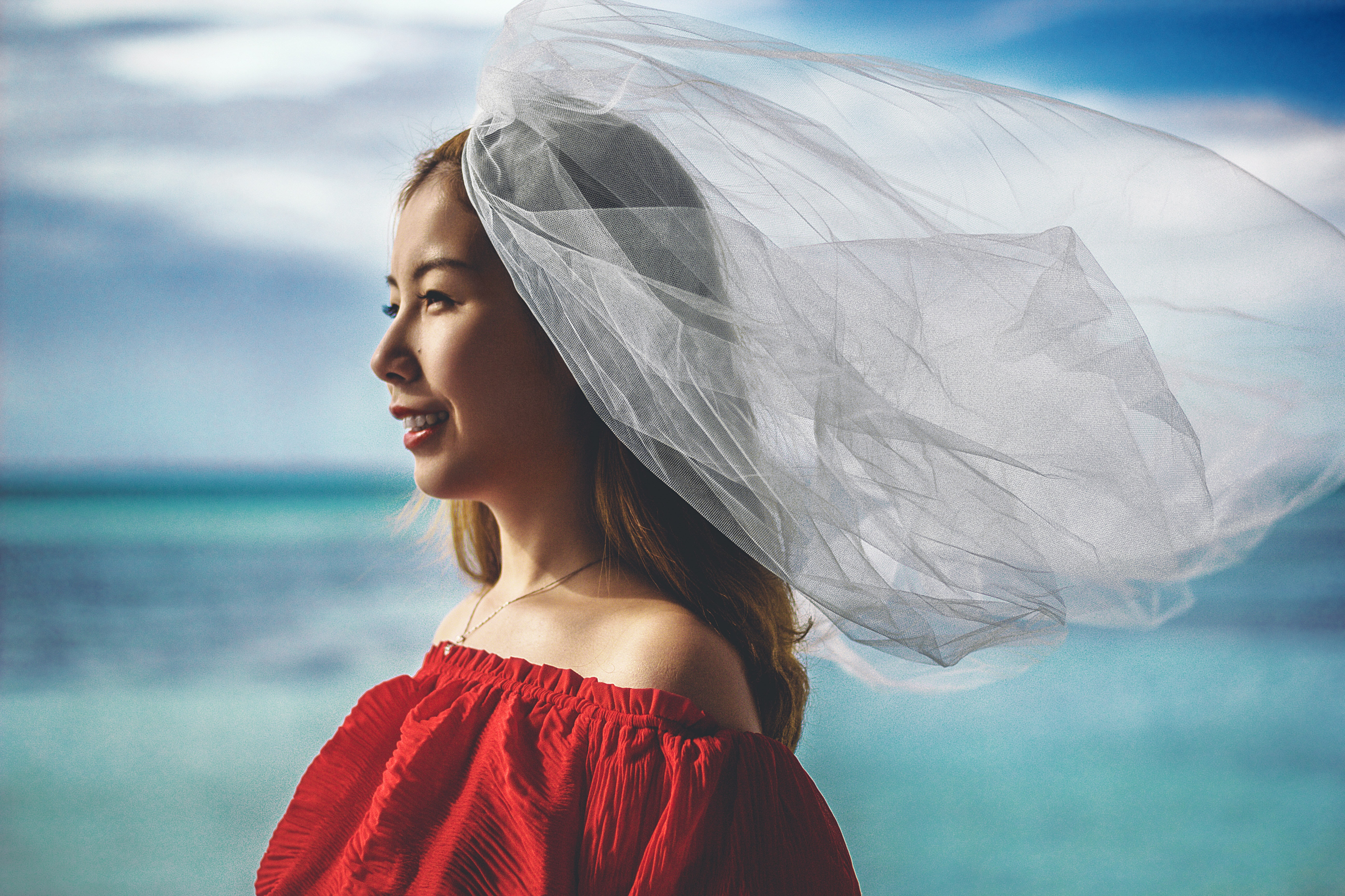 A bride wearing a red dress and veil smiles in front of blue water