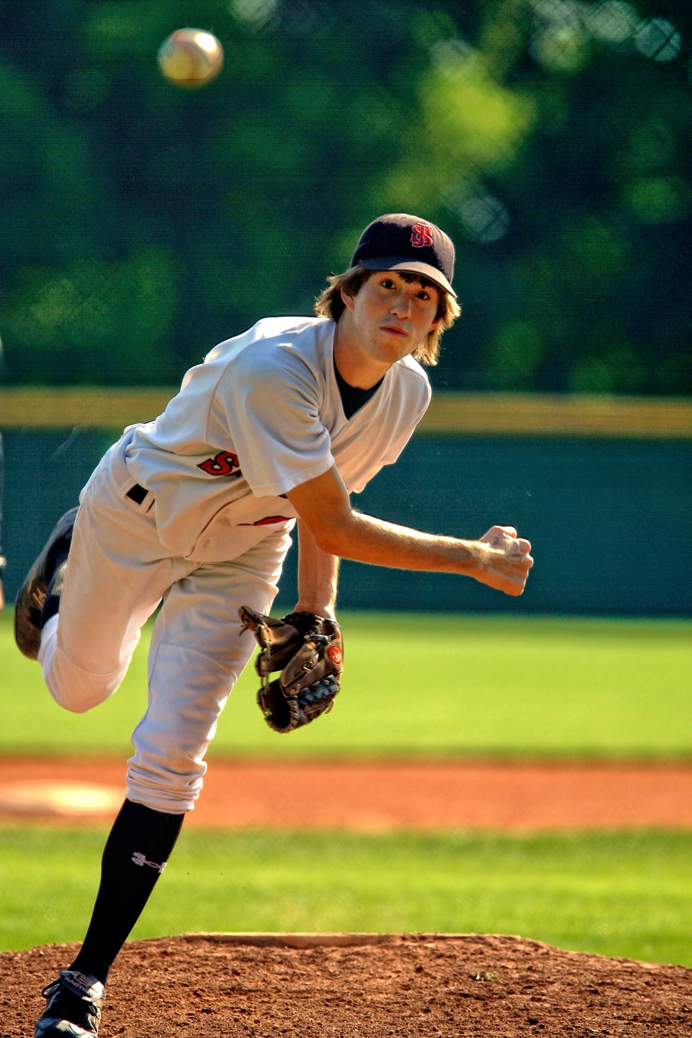 baseball pitcher throwing some fast ball pitch