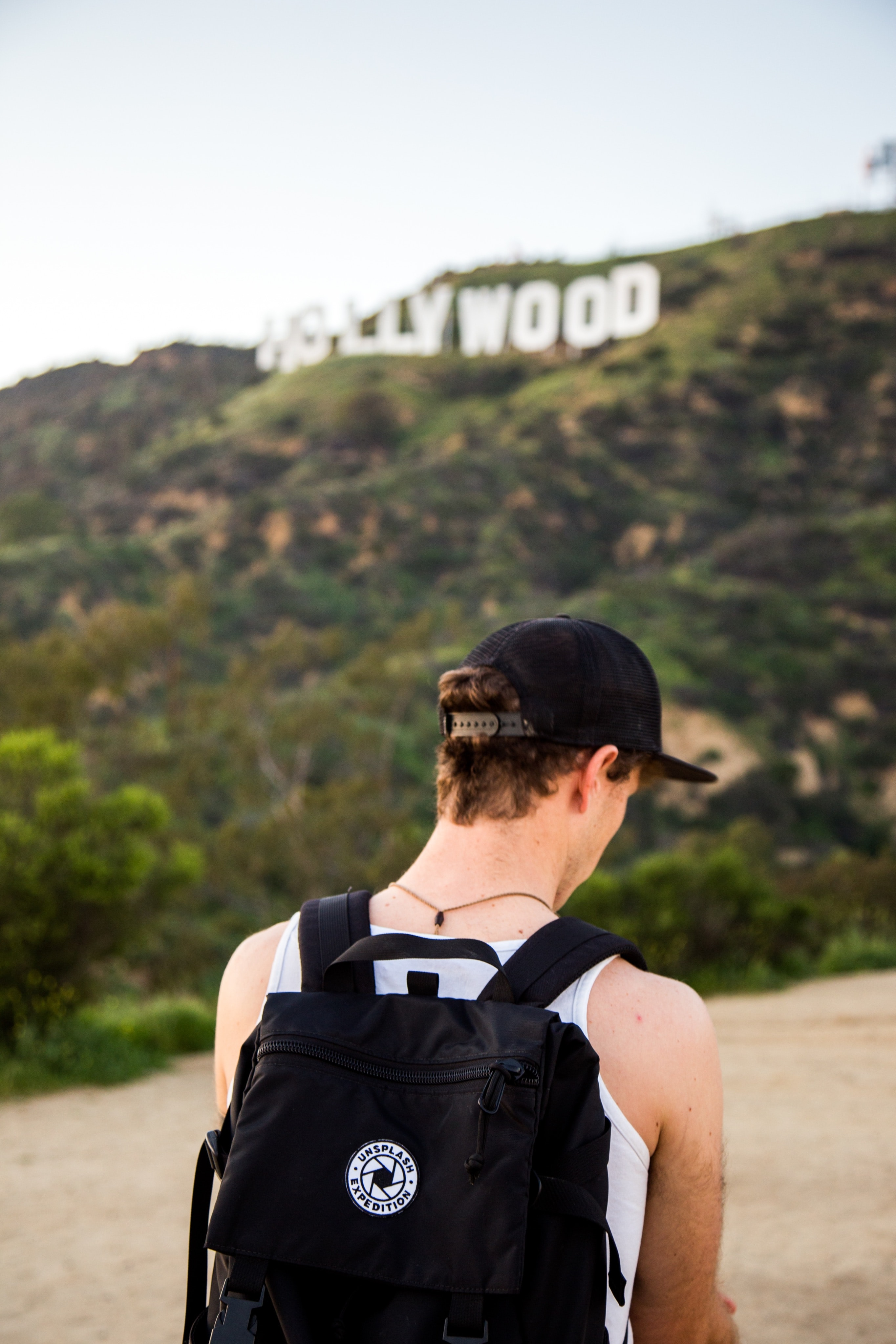 Tourist with a backpack walks toward the Hollywood sign in LA