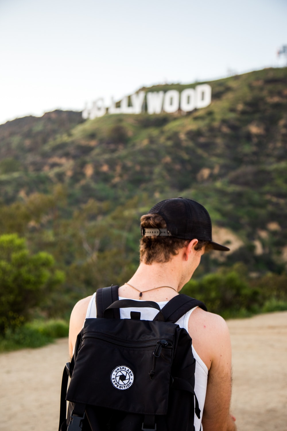 man wearing white tank top and black snapback cap carrying black backpack in distance hollywood signboard at daytime