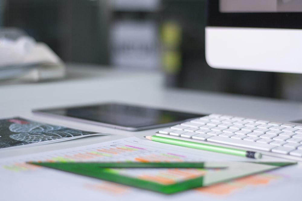 silver iMac near Magic Keyboard and green measuring tool