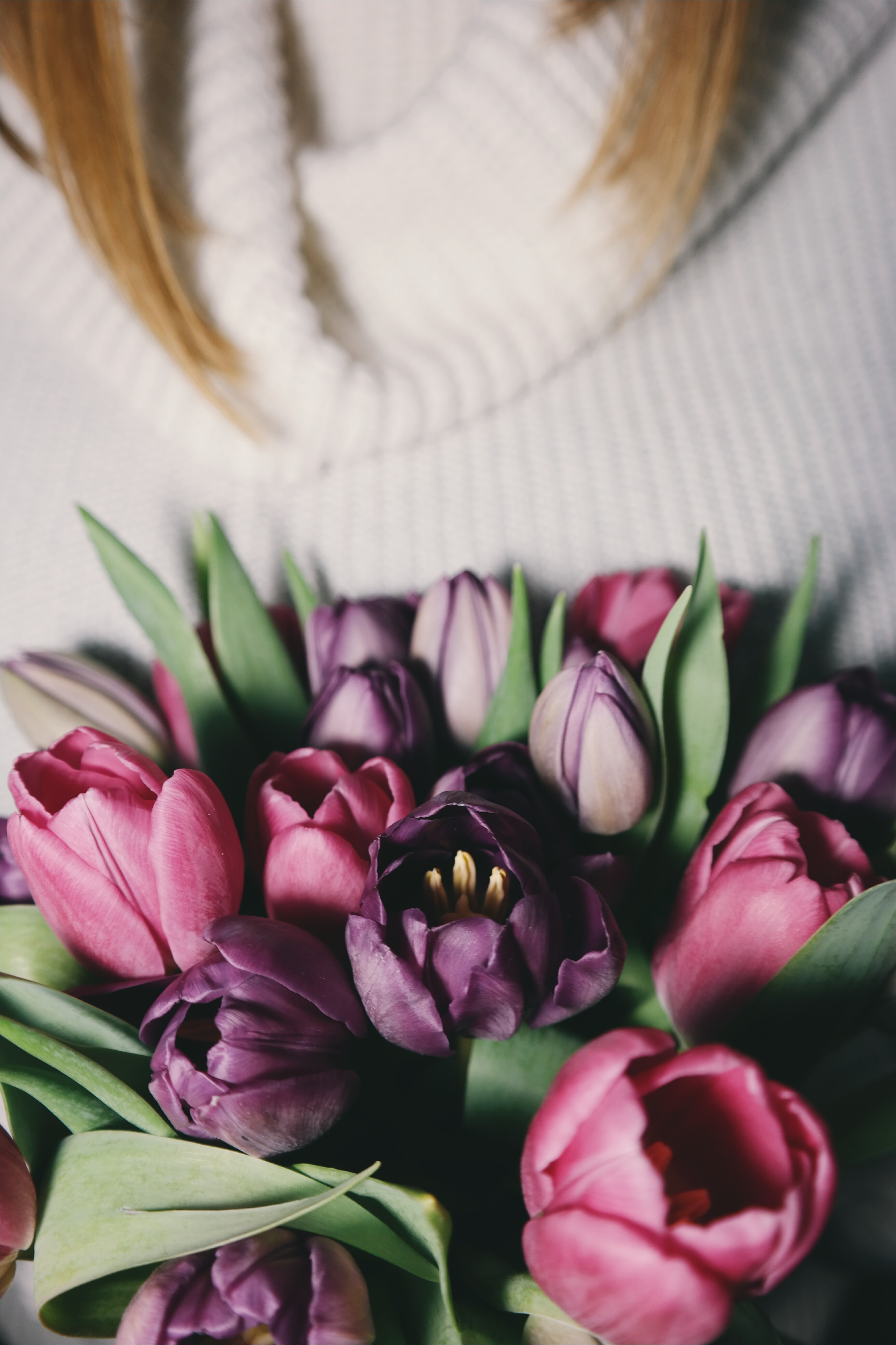 Pink purple flower bouquet with blonde woman in white cowl neck jumper in background in Spring