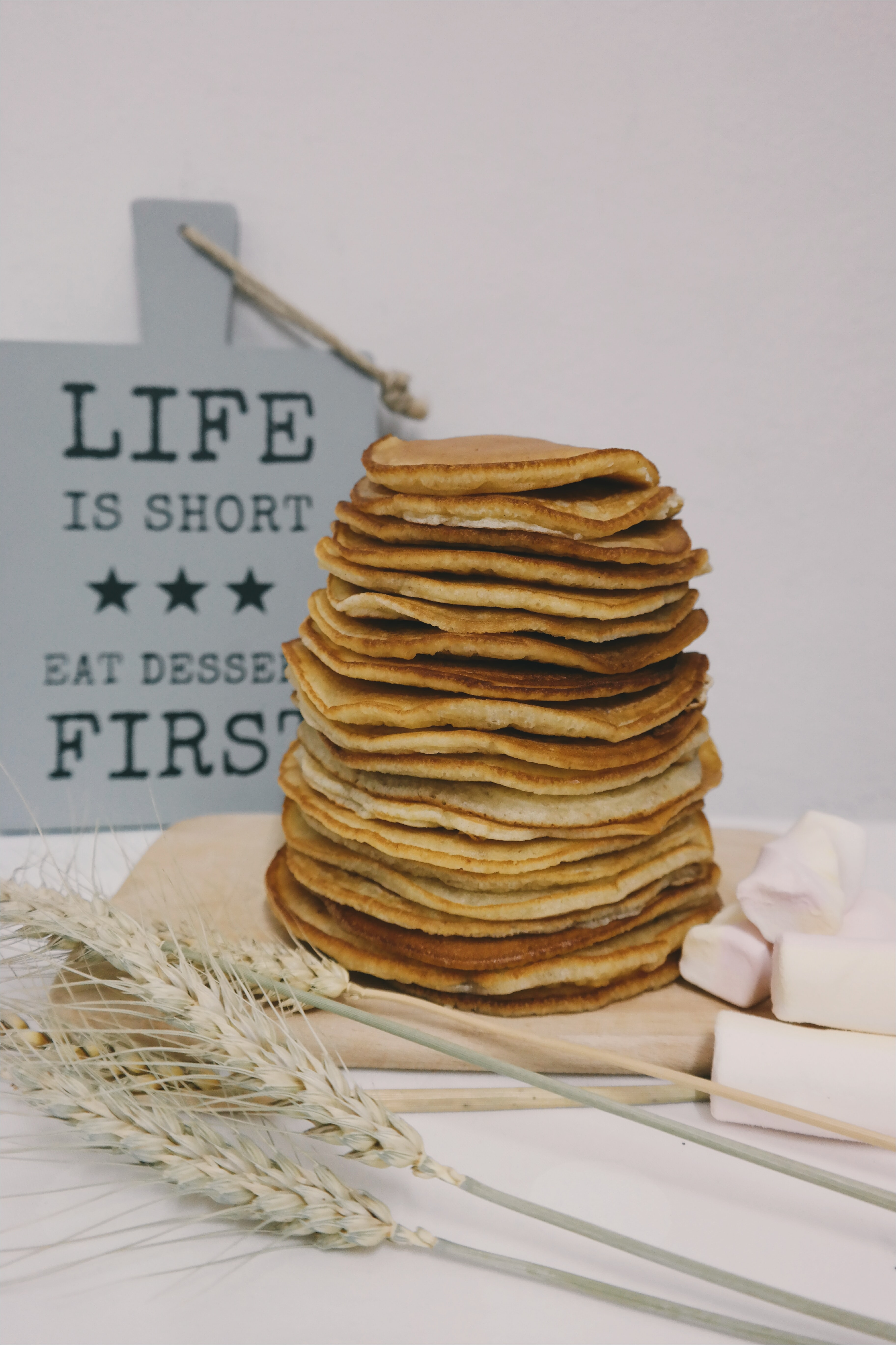 "A pile of pancakes in front of a blue sign that says ""Life is short - Eat pancakes first."""