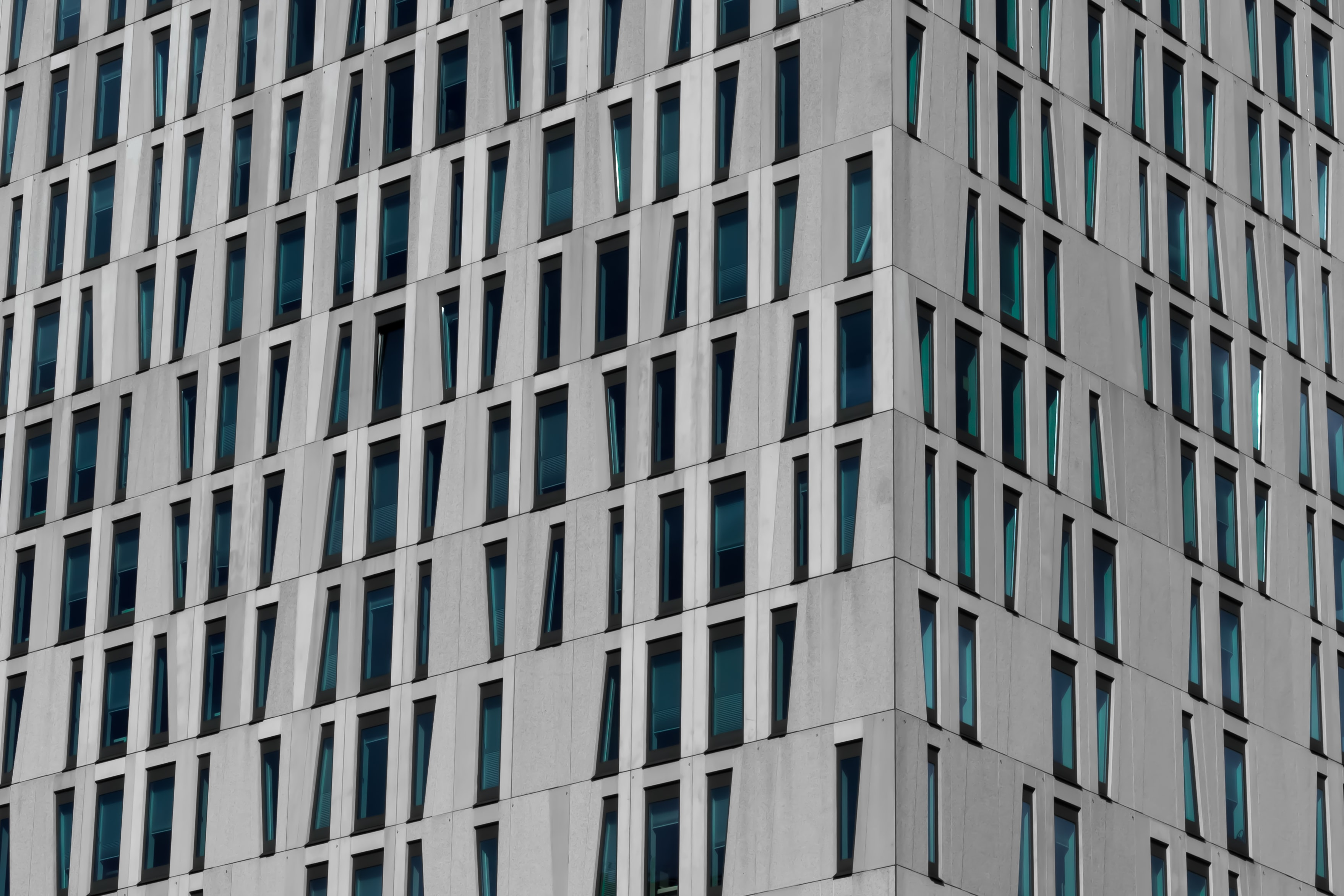 A gray building facade with windows in various shapes in Rotterdam