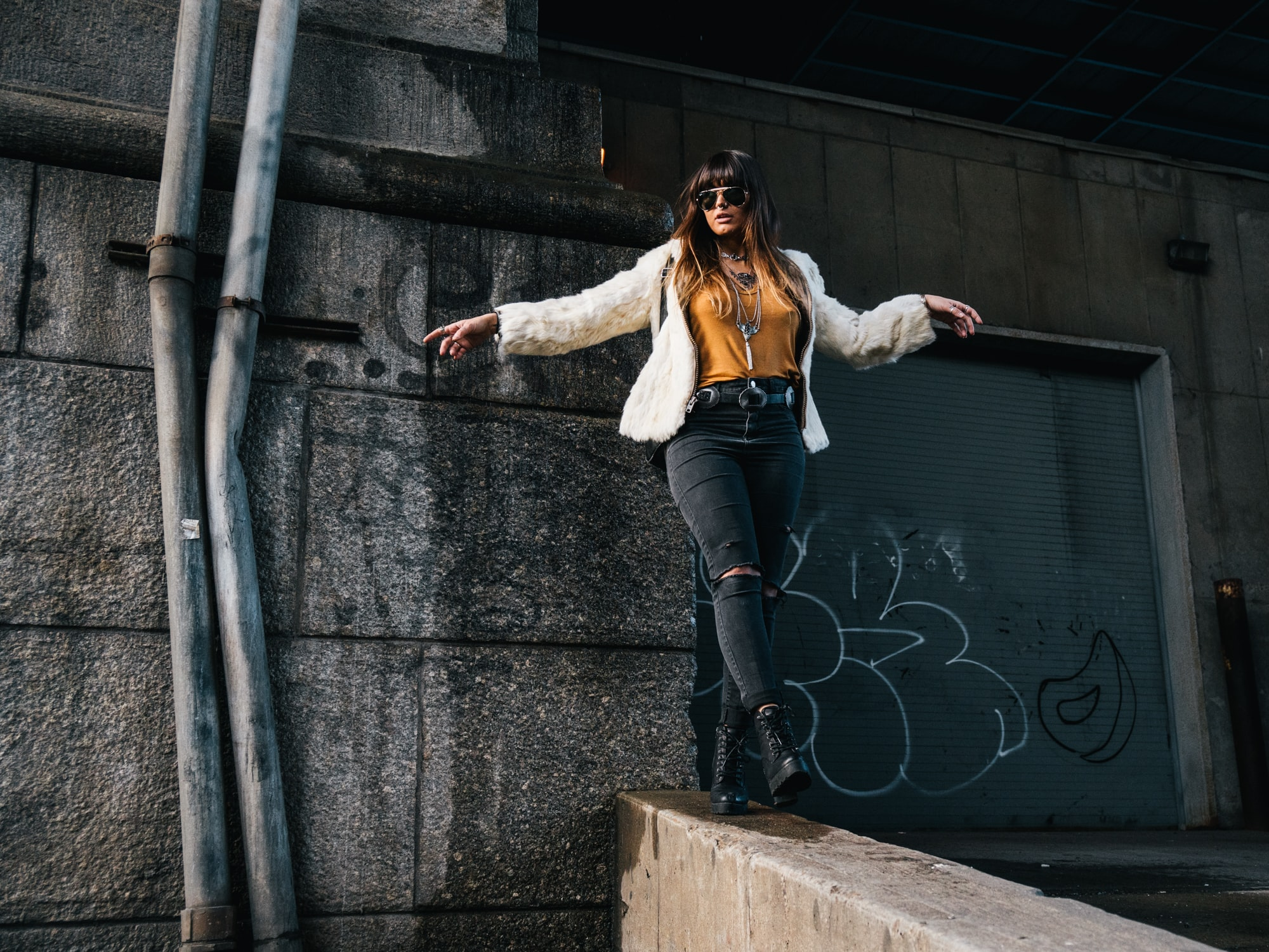 A woman wearing ripped jeans, combat boots, and a fur jacket walking on a wall in Chinatown