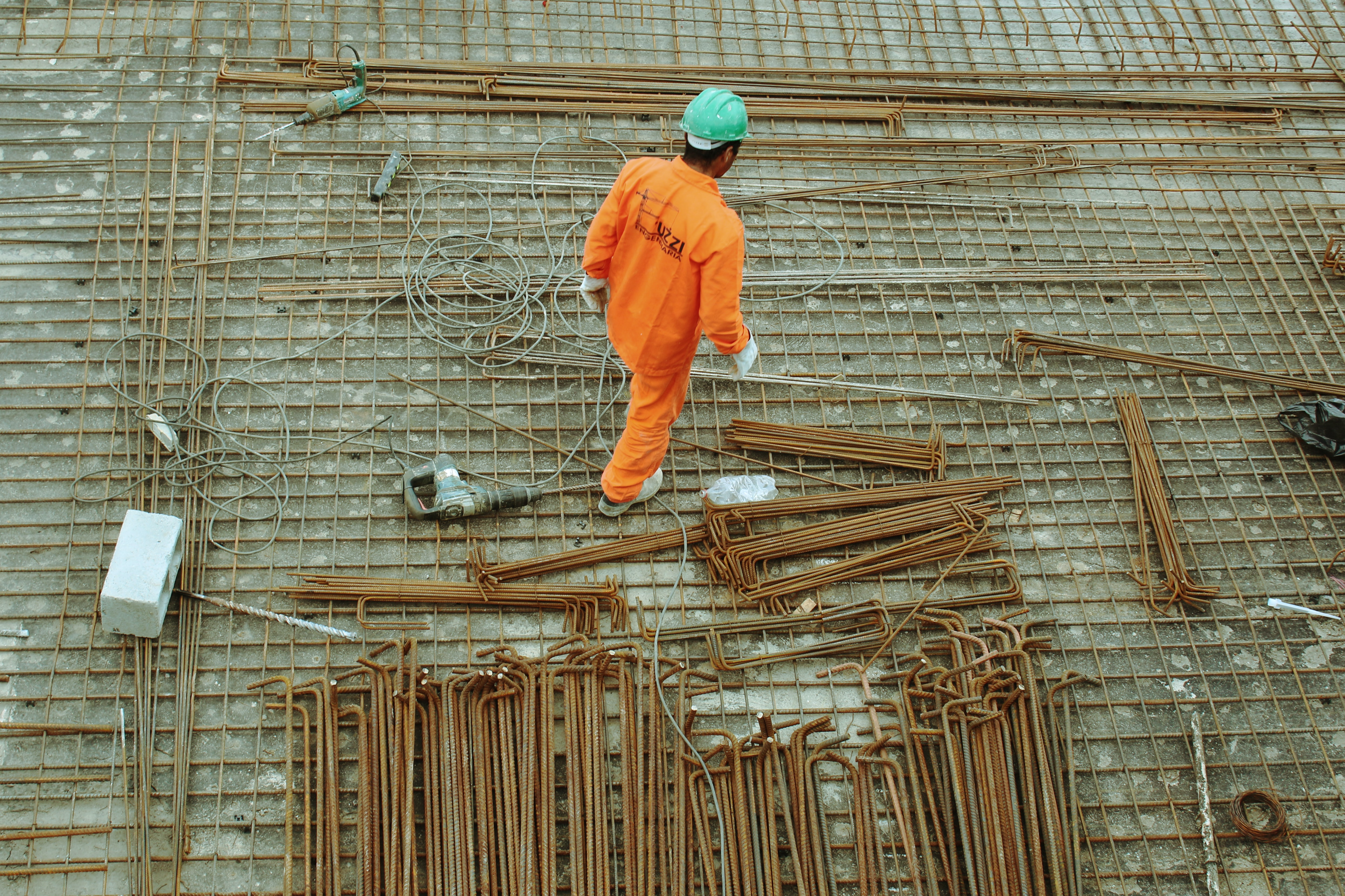 A construction worker near metal rods at a construction site
