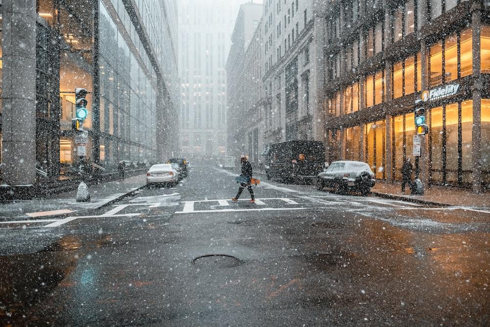 person walking on pedestrian lane near vehicles between buildings while raining at daytime
