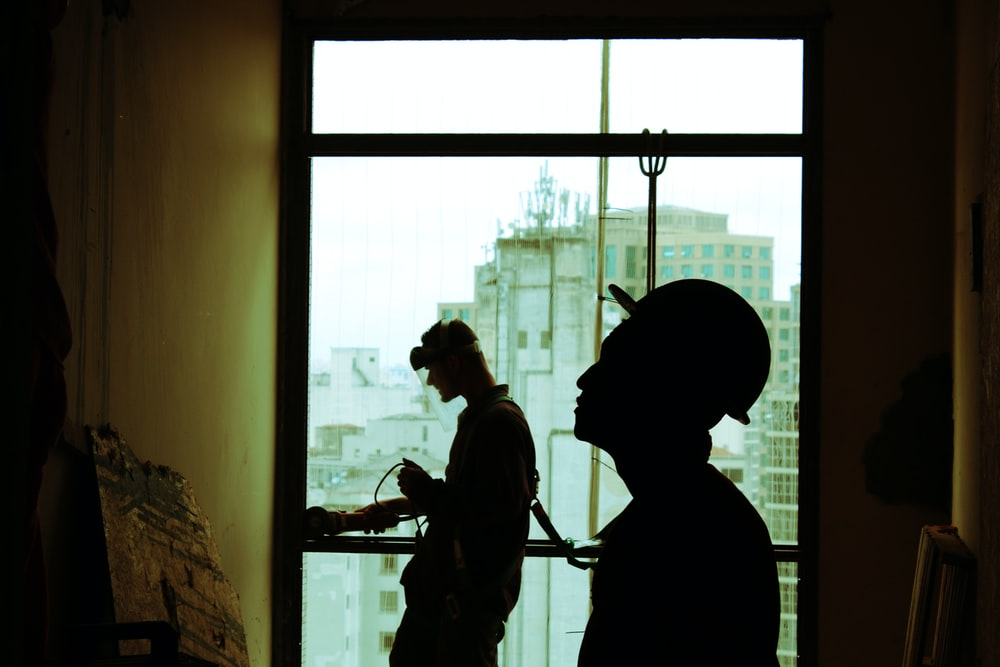 two men wearing hard hat standing near clear glass window