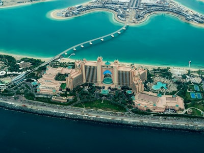 aerial photography of concrete buildings on the middle of the sea dubai teams background