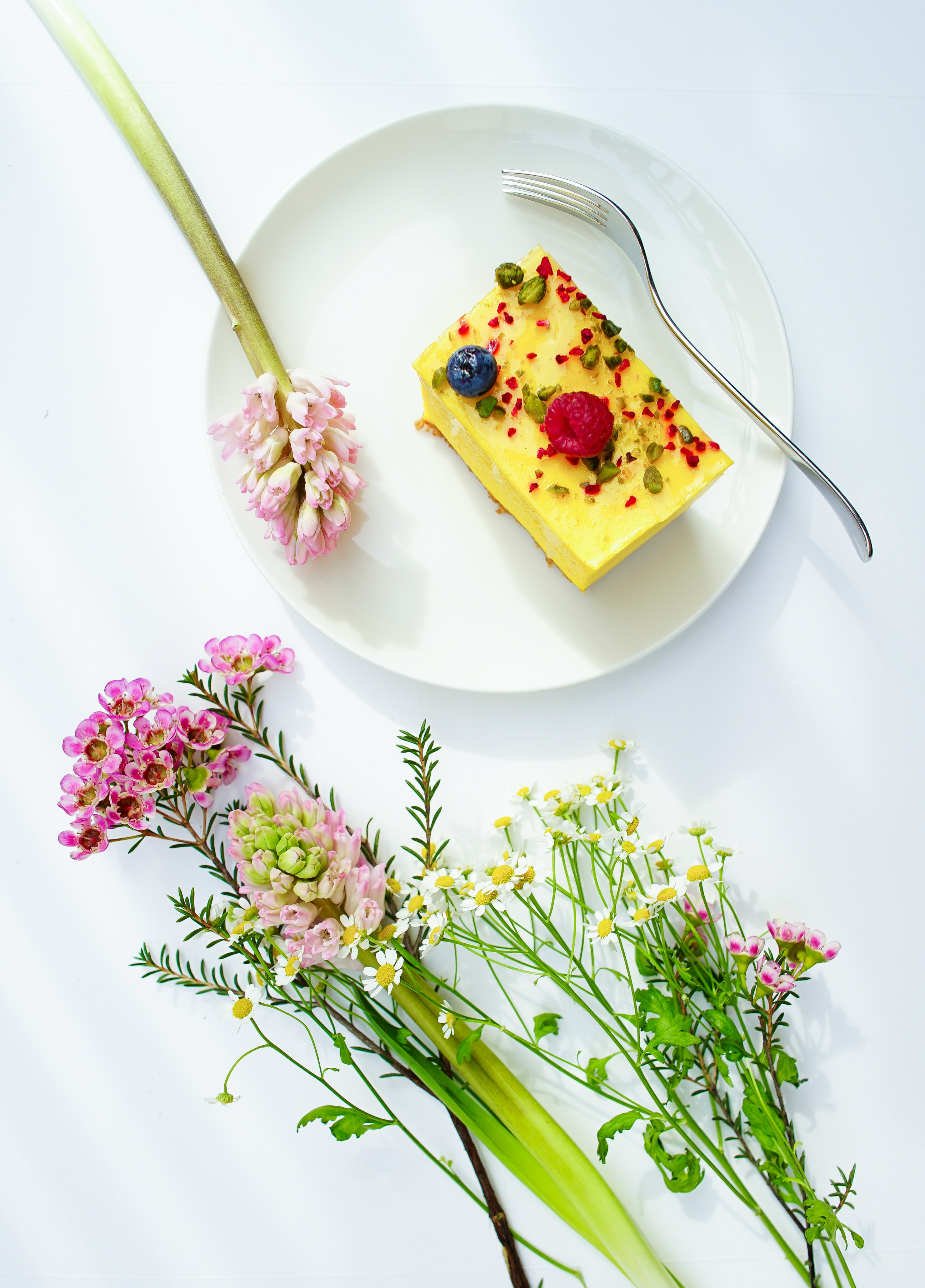 An overhead shot of a piece of cheesecake on a plate next to small bouquets of various flowers