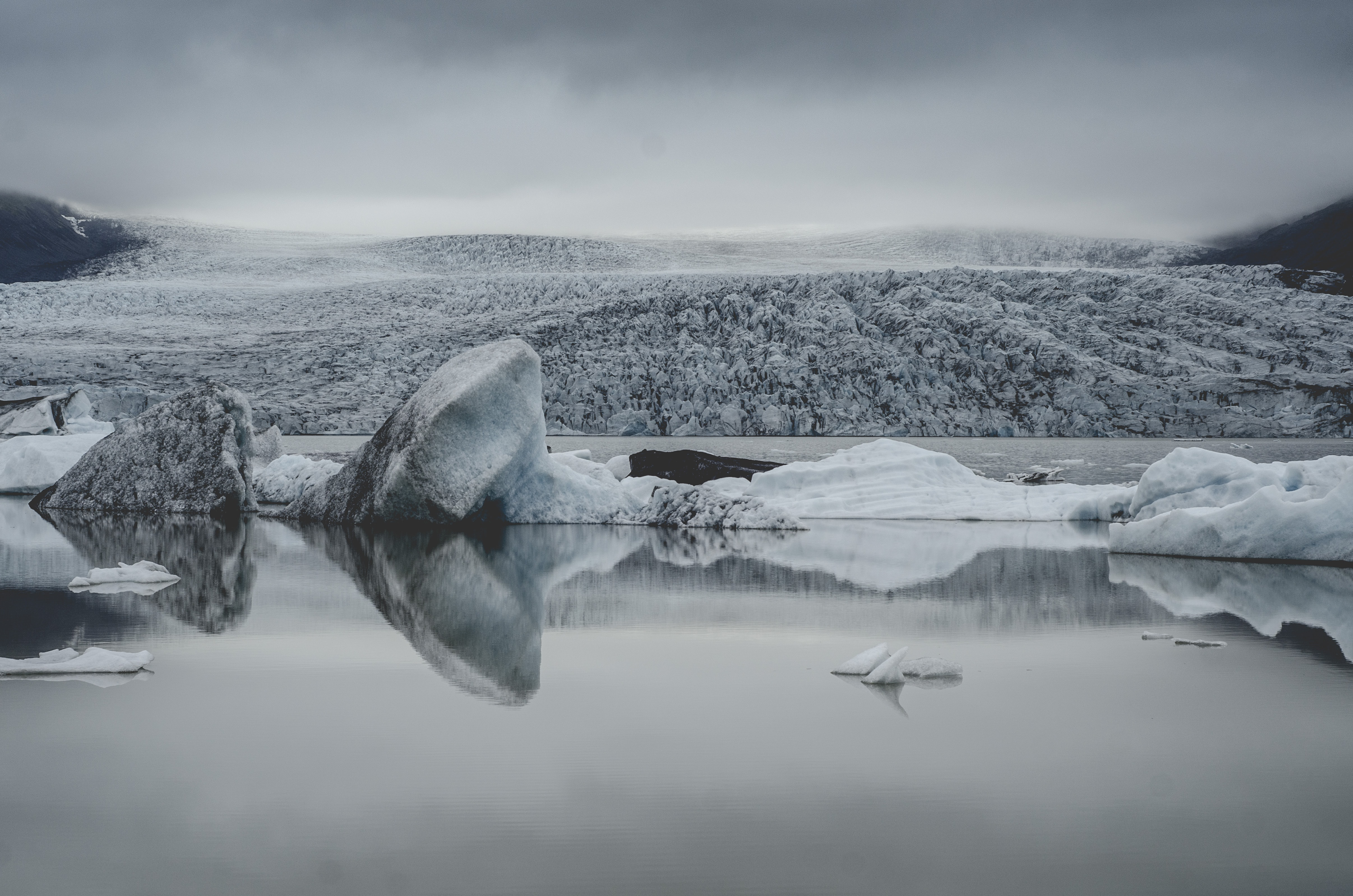 A still lake with glaciers jutting out with a snowy wilderness receding into the horizon