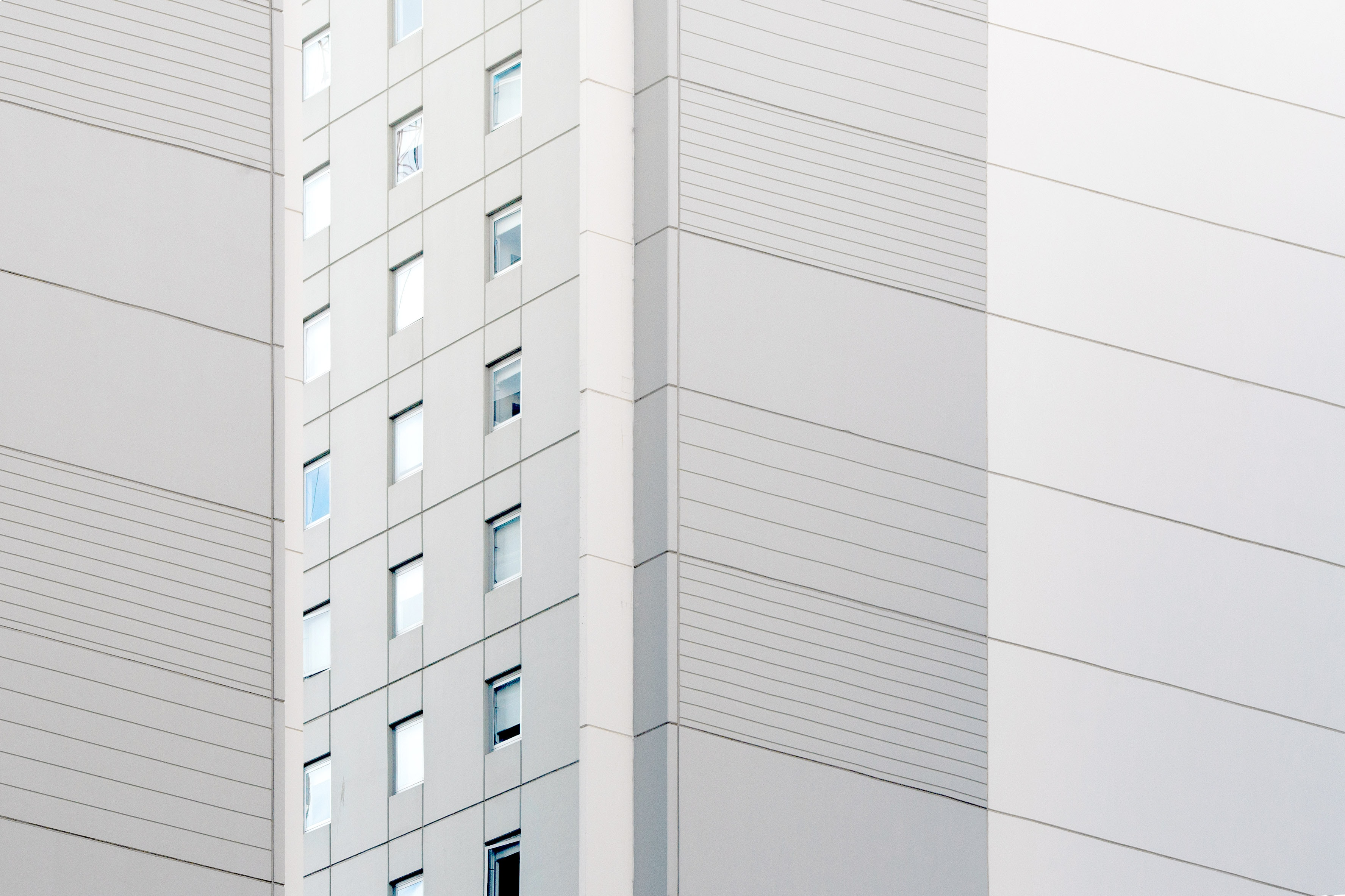 A white and gray facade of an apartment building