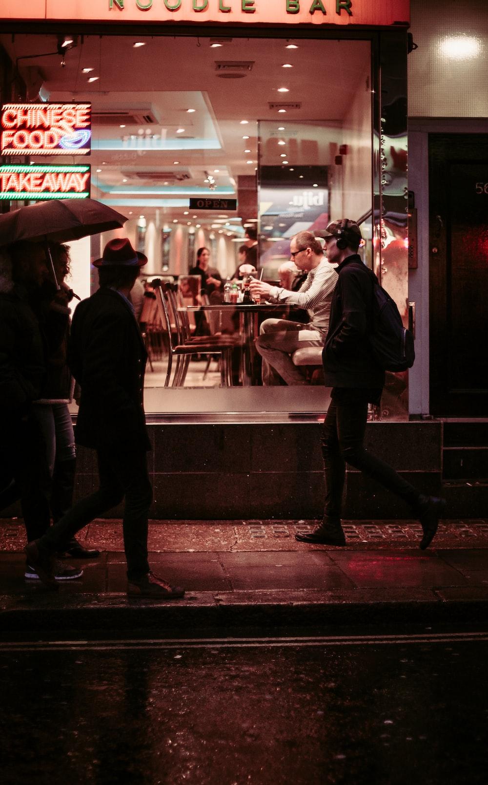 man walking near restaurant wearing jacket