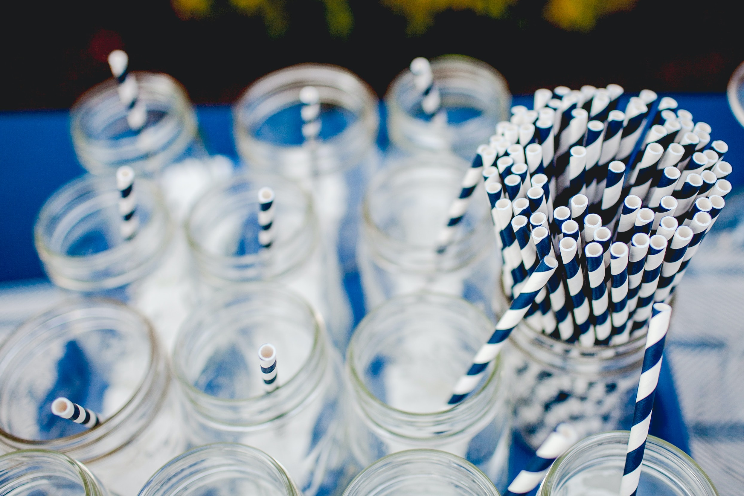 A selection of Mason jars with blue and white striped straws, ahead of a party
