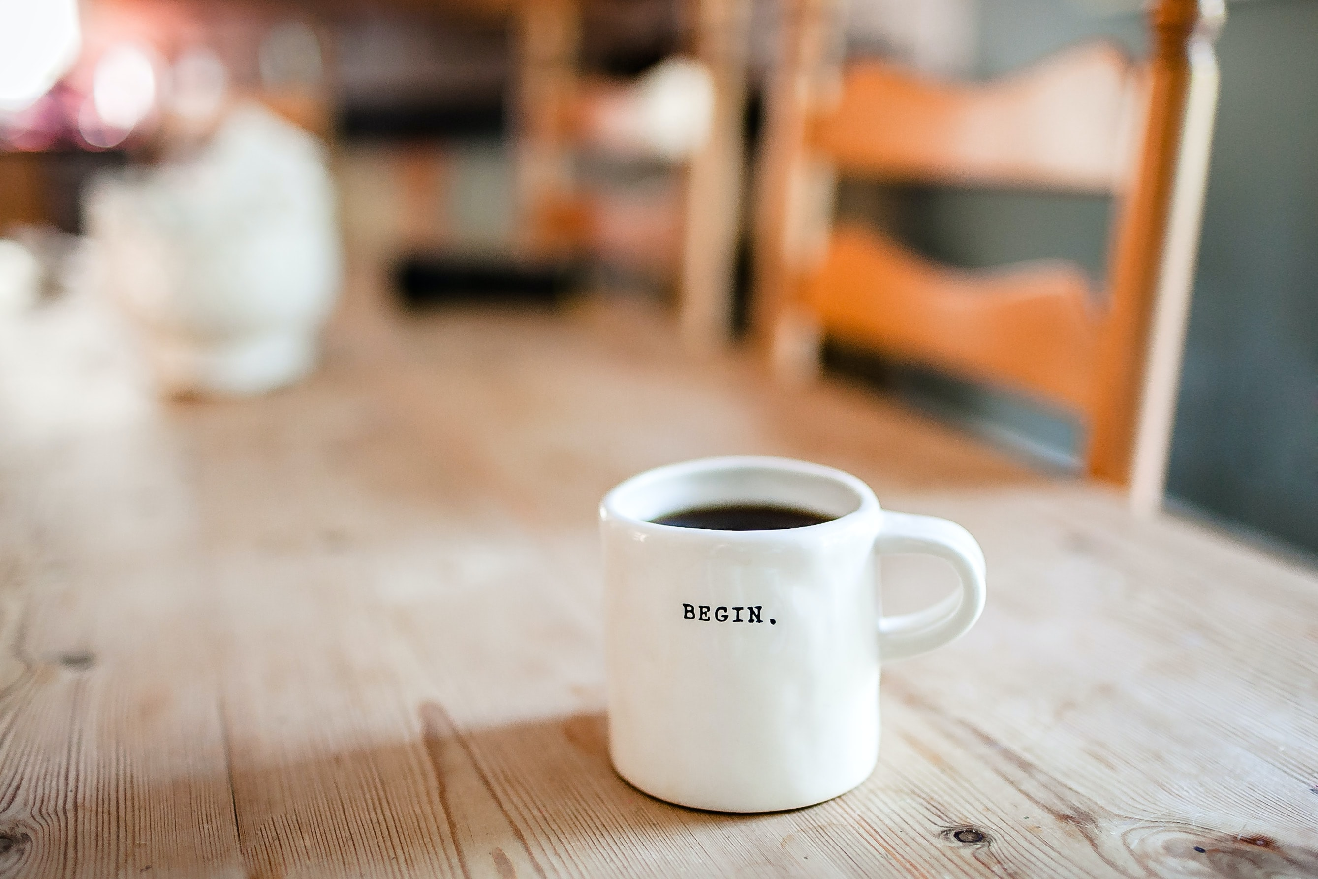 """A white coffee mug with """"begin"""" written on it on a wooden table"""