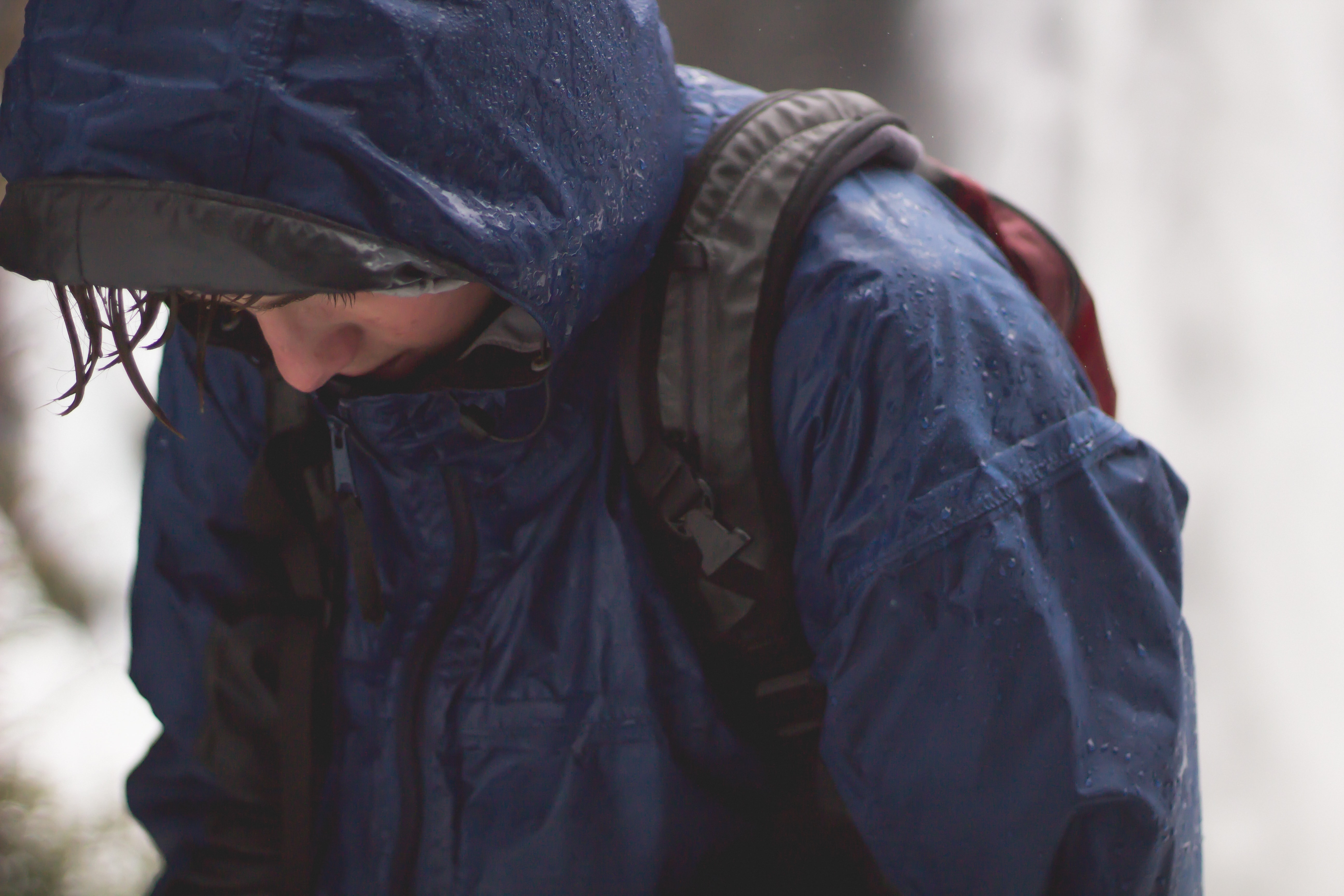 A wet person in a raincoat and backpack holds their head down