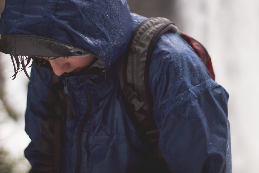 person in blue raincoat and black backpack walking with head low