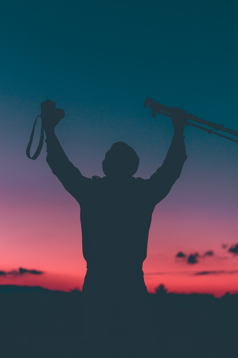 silhouette of a person raising camera and tripod with pink and blue sky
