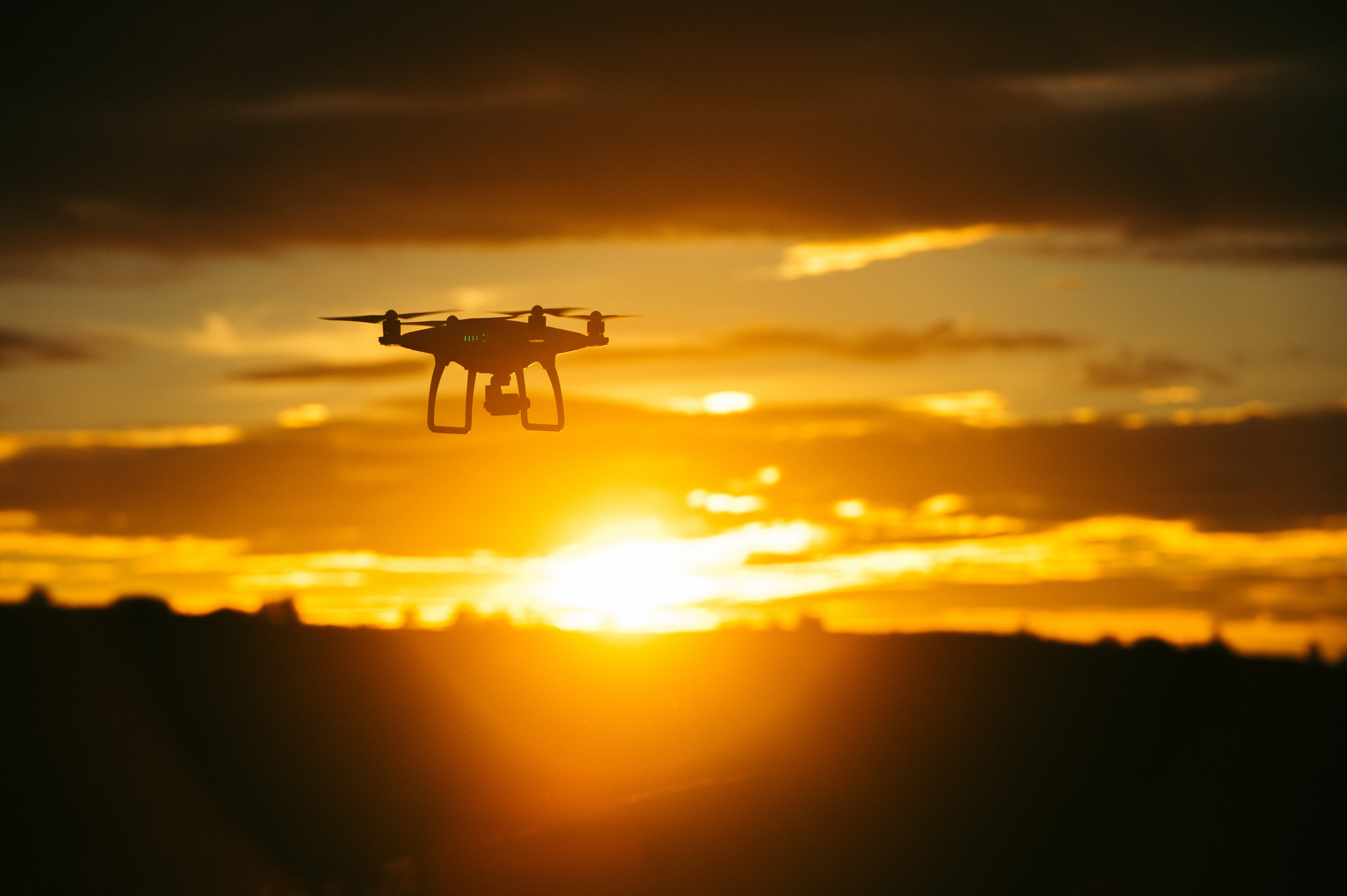 View of a flying drone in focus with a sunrise-or-sunset background making the floor dark and the cloudy sky orange